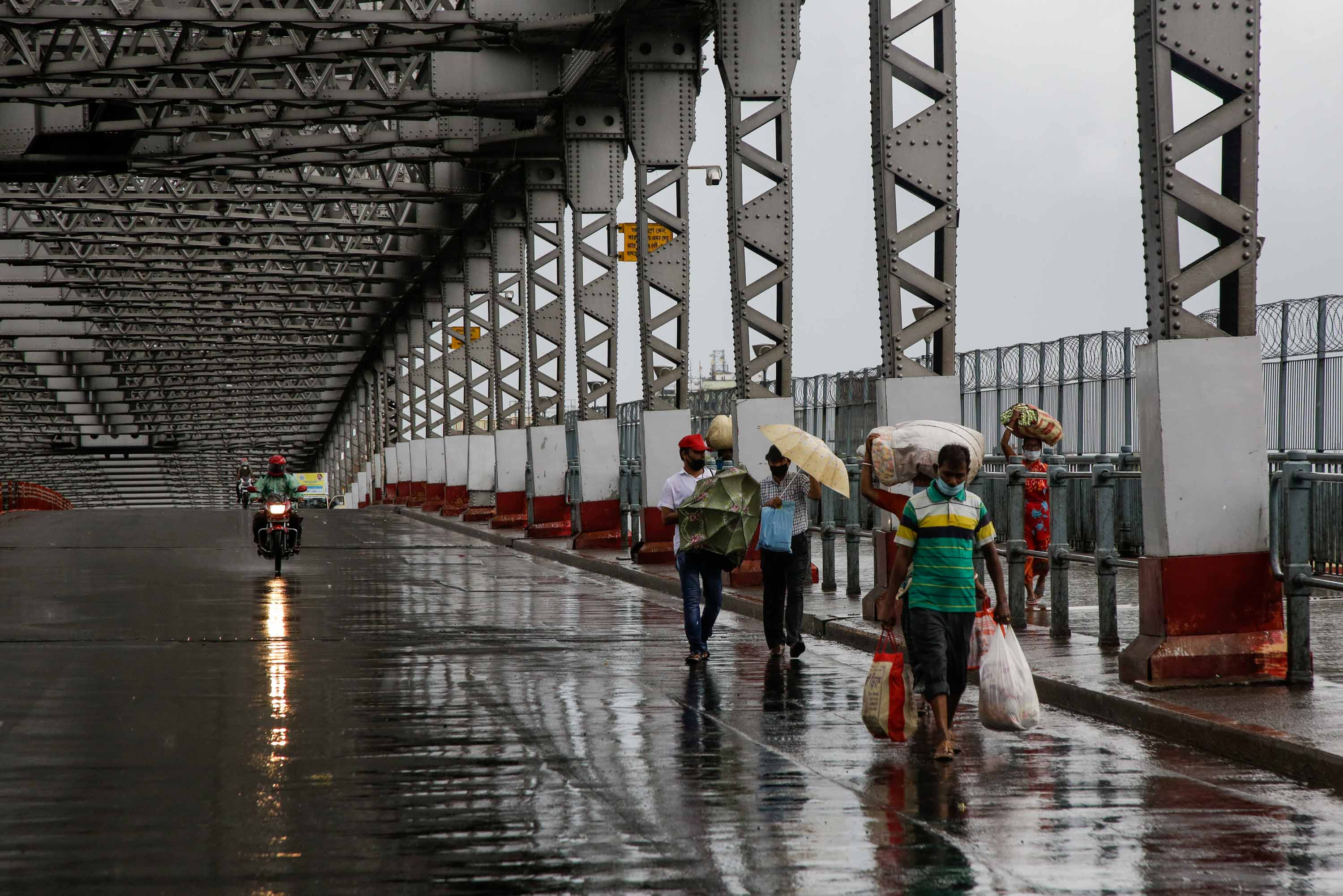 Commuters walk along the city's iconic landmark, Howrah Bridge to cross the Hooghly River as it rains in Kolkata, India, on May 20.