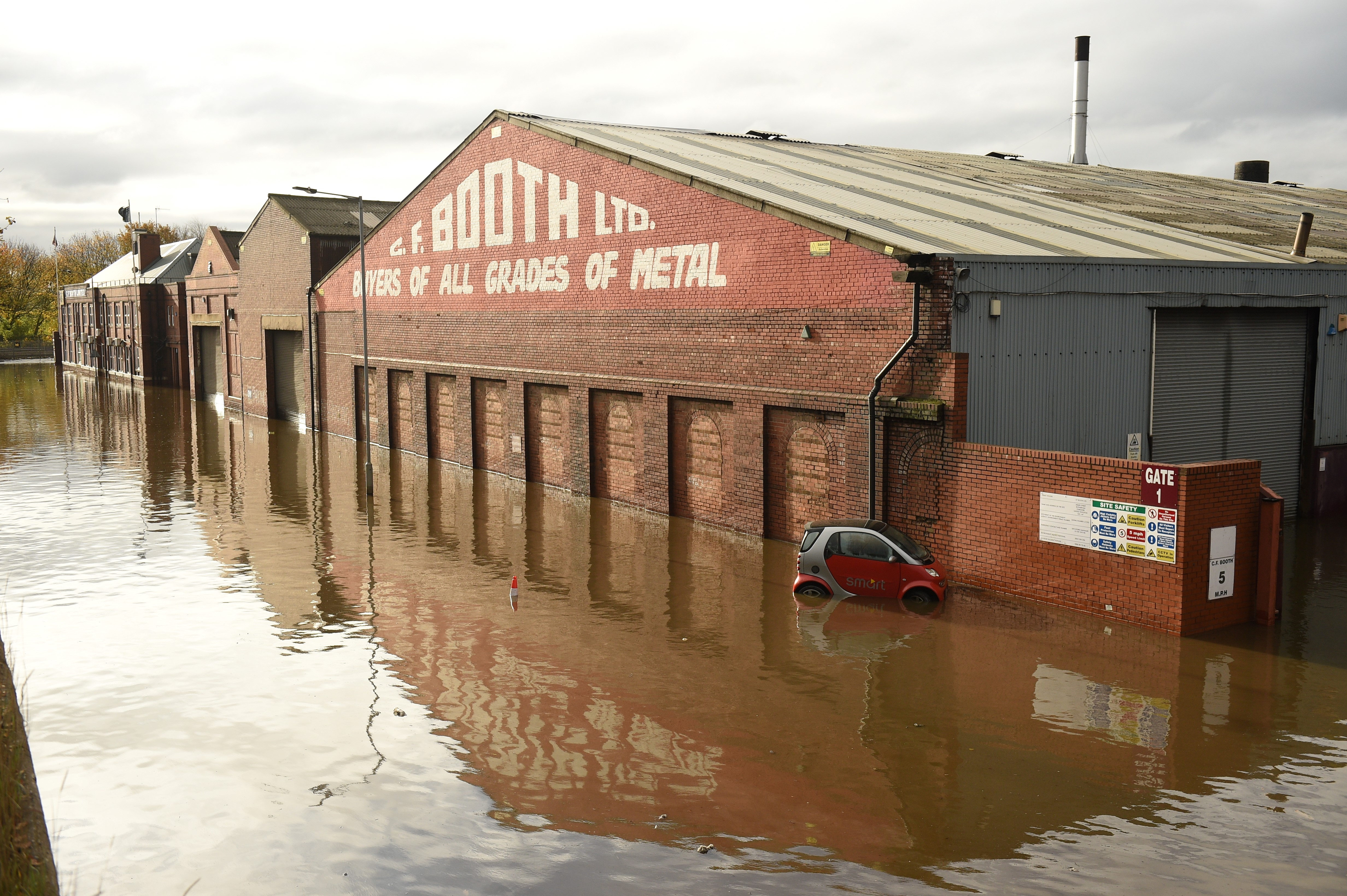 An abandoned car is pictured in flood water surrounding buildings in Rotherham, following flash flooding.