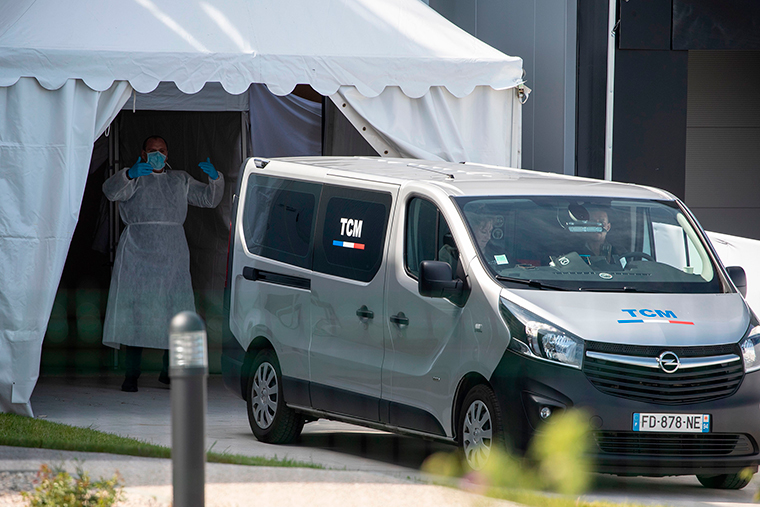A funeral services van brings coffins in a building turned into a new 'large capacity' morgue in Wissous, France, on Sunday, April 19.