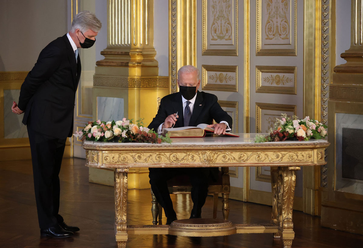 US President Joe Biden signs a book during his meeting with King Philippe at the Royal Palace of Brussels on June 15.