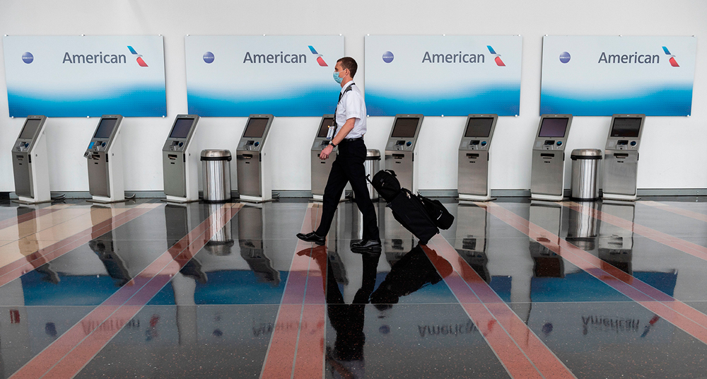 An airline employee walks past empty American Airlines check-in terminals at Ronald Reagan Washington National Airport in Arlington, Virginia, on May 12.
