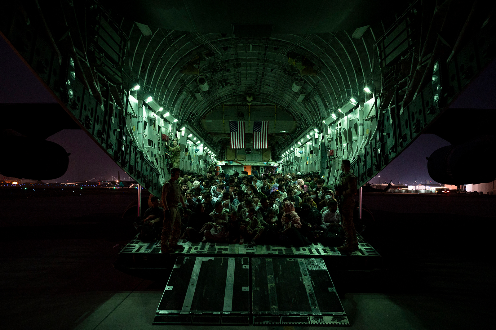 In this handout provided by the U.S. Air Force, an air crew assigned to the 816th Expeditionary Airlift Squadron assists evacuees aboard a C-17 Globemaster III aircraft in support of the Afghanistan evacuation at Hamid Karzai International Airport on August 21 in Kabul, Afghanistan.