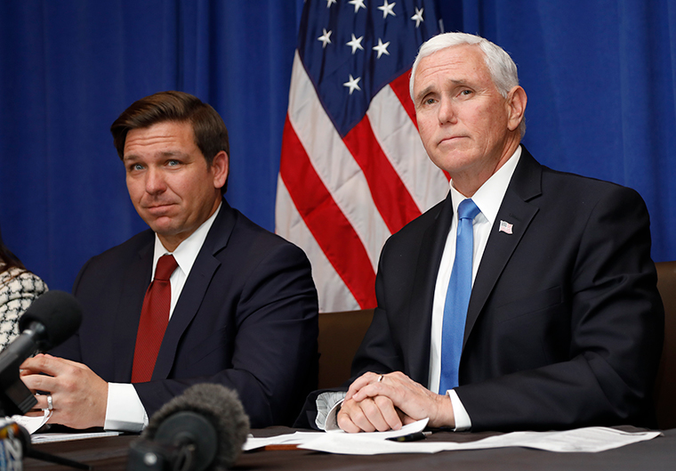 Florida Gov. Ron DeSantis and Vice President Mike Pence, right, take questions during a Florida Coronavirus Response Meeting, at the West Palm Beach International Airport, Friday, February 28, in West Palm Beach, Florida.