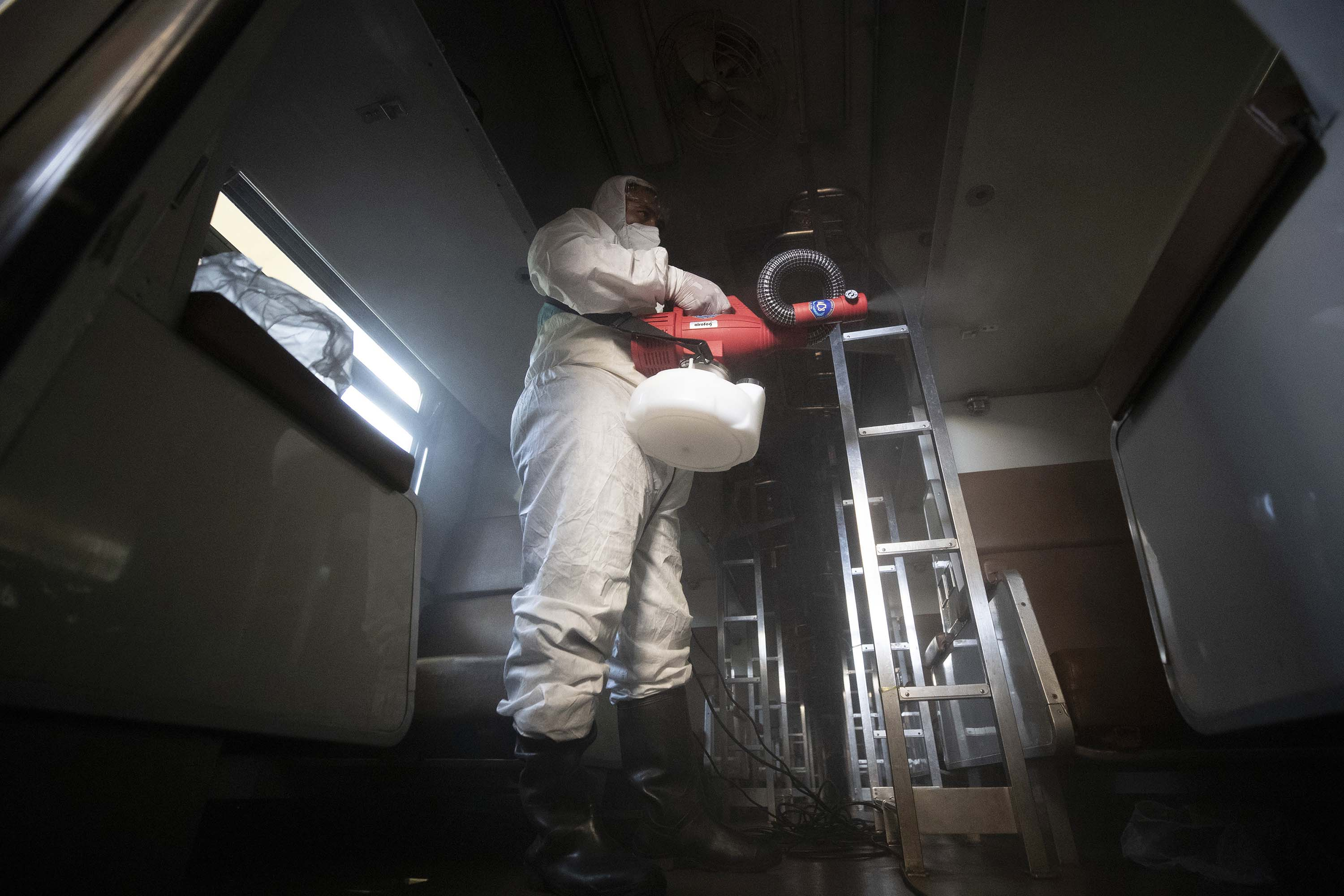 A worker disinfects a train in effort to prevent the spread of the coronavirus, at Hua Lamphong Railway Station in Bangkok, Thailand, on Friday.