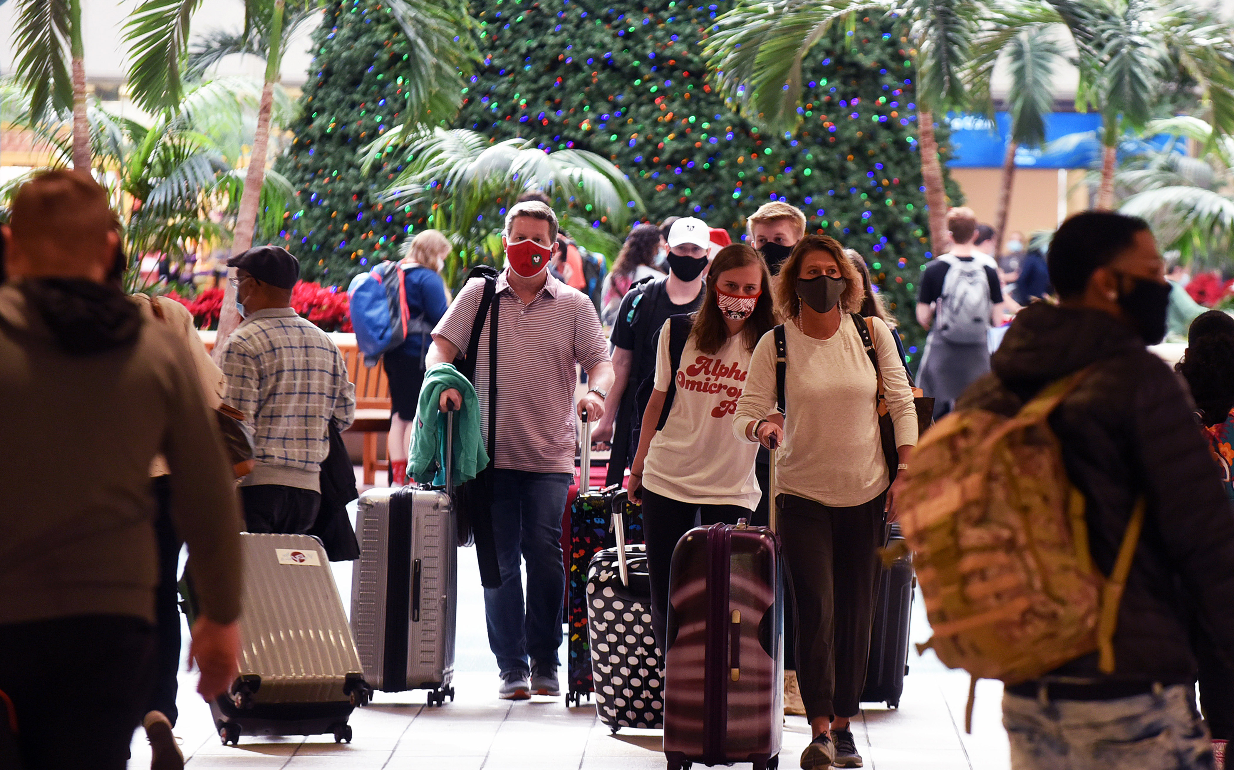 Travelers wearing face masks arrive at Orlando International Airport in Florida, on December 24.