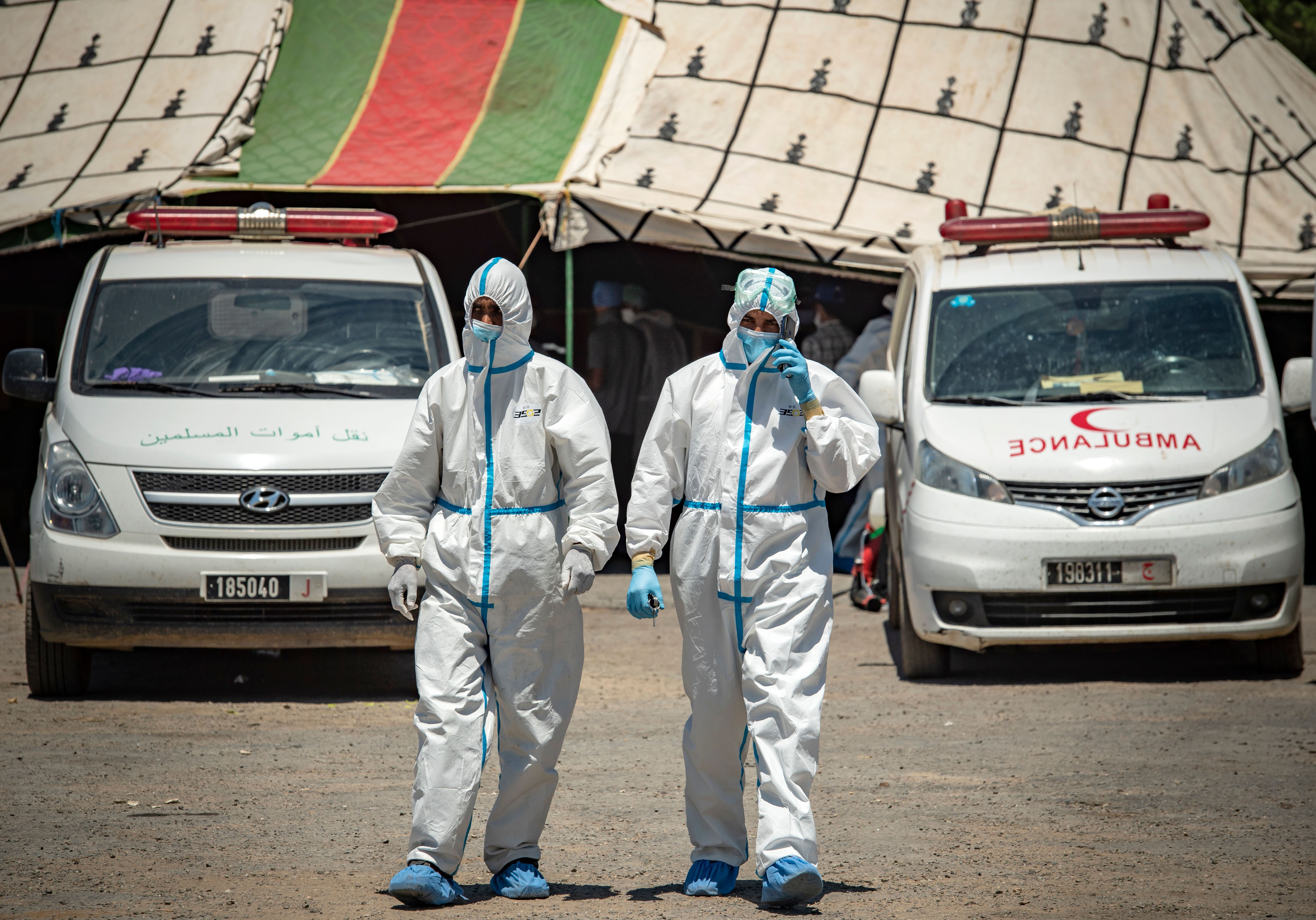 Members of a medical team wait to transfer people who tested positive for Covid-19 at a parking lot in Moulay Bousselham, Morocco, on June 20.