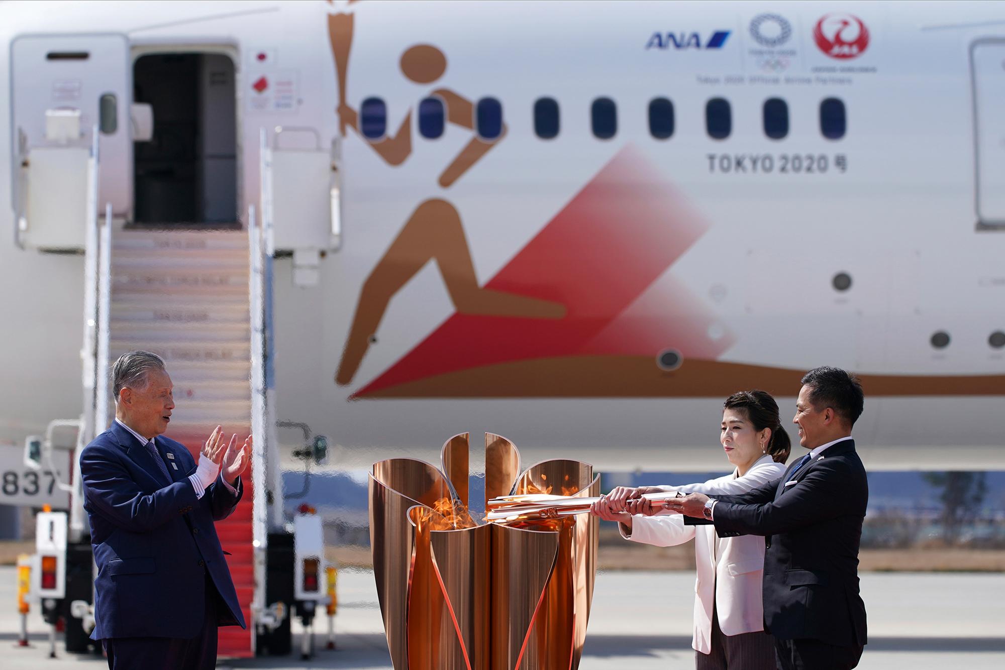 Three-time Olympic gold medalists Tadahiro Nomura, right, and Saori Yoshida light the torch as Tokyo 2020 Olympics chief Yoshiro Mori, far left, watches at the Japan Air Self-Defense Force's Matsushima Base in Higashimatsushima, Japan, on Friday, March 20.