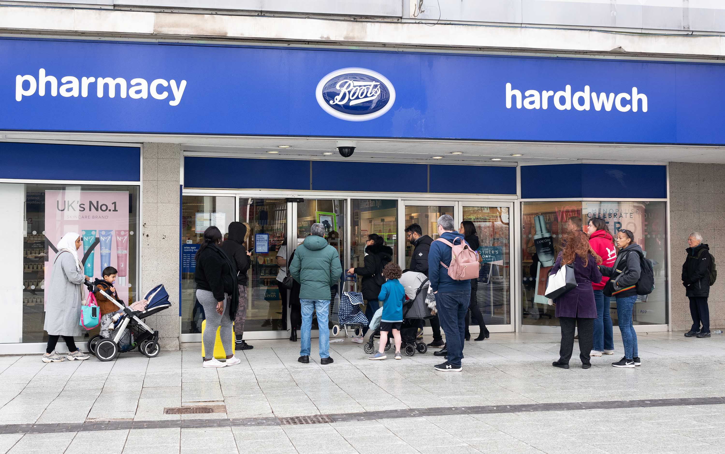 Shoppers wait for a Boots pharmacy store to open on March 8, in Cardiff, Wales.
