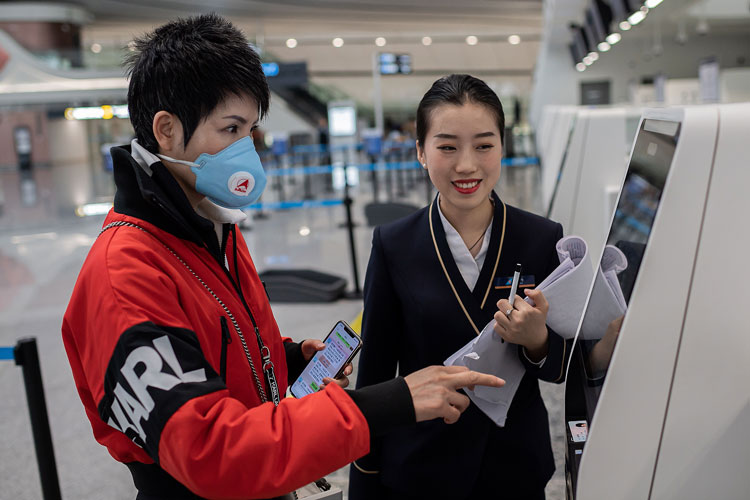 A traveller receives check-in assistance from airline staff at the Daxing International Airport.