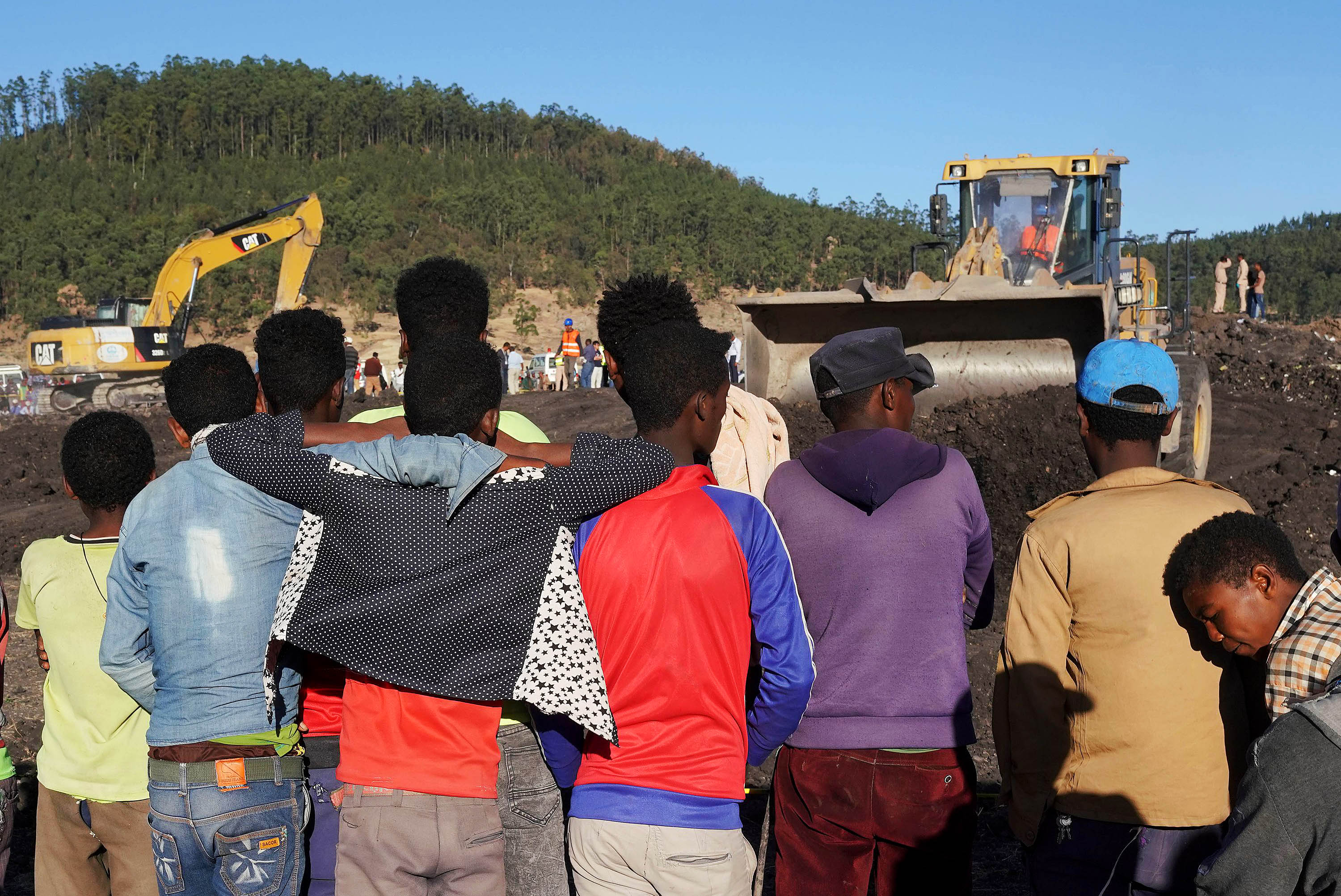 Local residents watch as recovery personnel scour the crater where Ethiopian Airlines Flight 302 went down.
