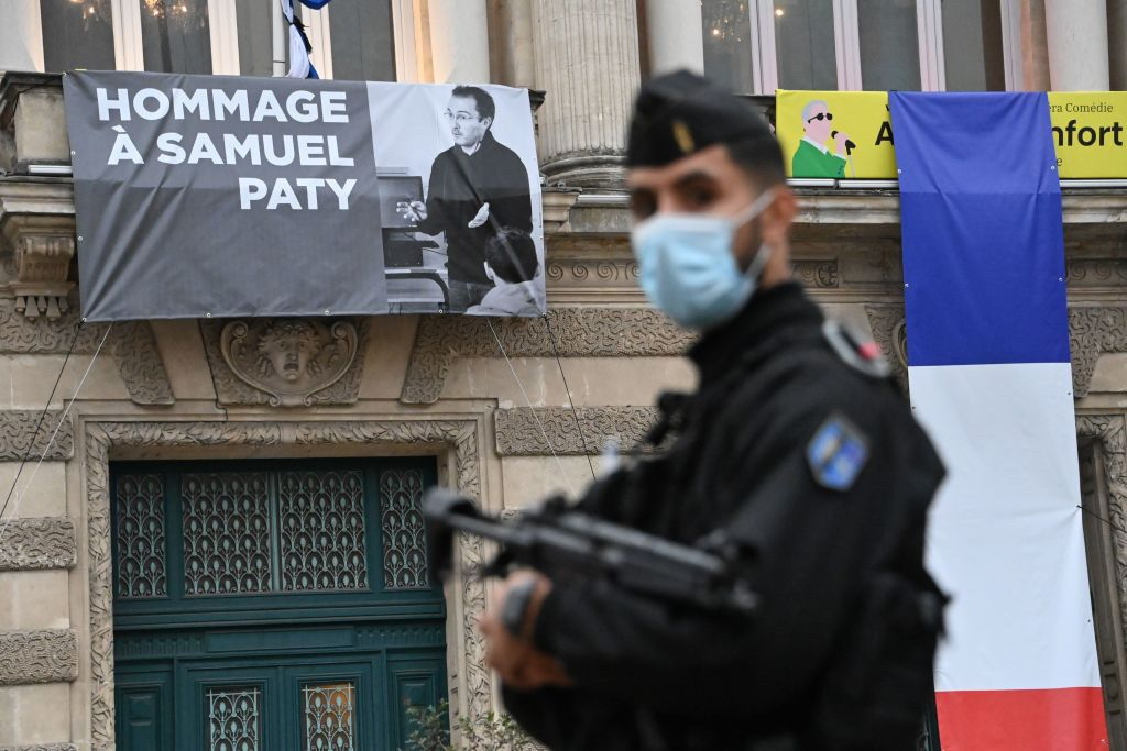 A police officer stands in front of a portrait of Samuel Paty, in Montpellier, France, on October 21. Paty was killed earlier this month.
