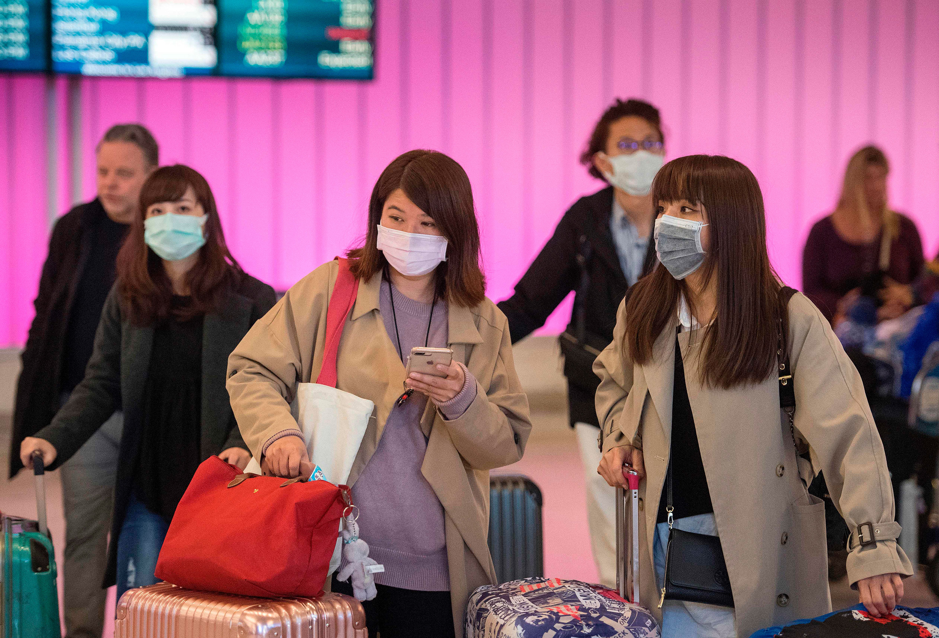TOPSHOT - Passengers at the Los Angeles International Airport wear protective masks on January 22.