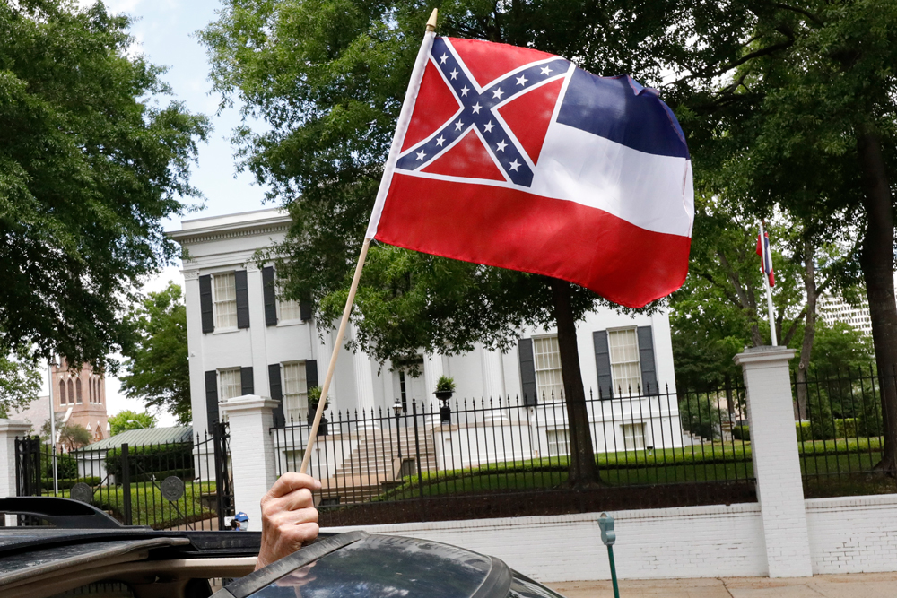 """In this April 25 photograph, a small Mississippi state flag is held by a participant during a drive-by """"re-open Mississippi"""" protest past the Governor's Mansion, in the background, in Jackson, Mississippi."""