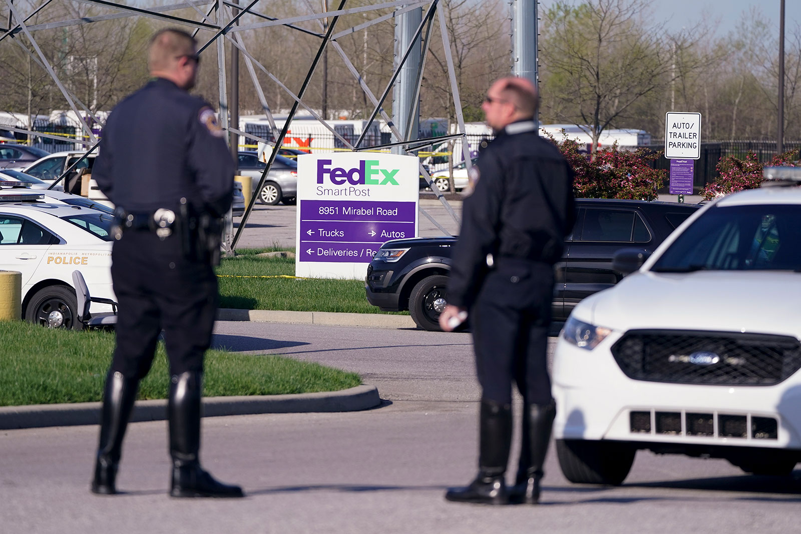 Police stand outside the Indianapolis FedEx facility on Friday morning.