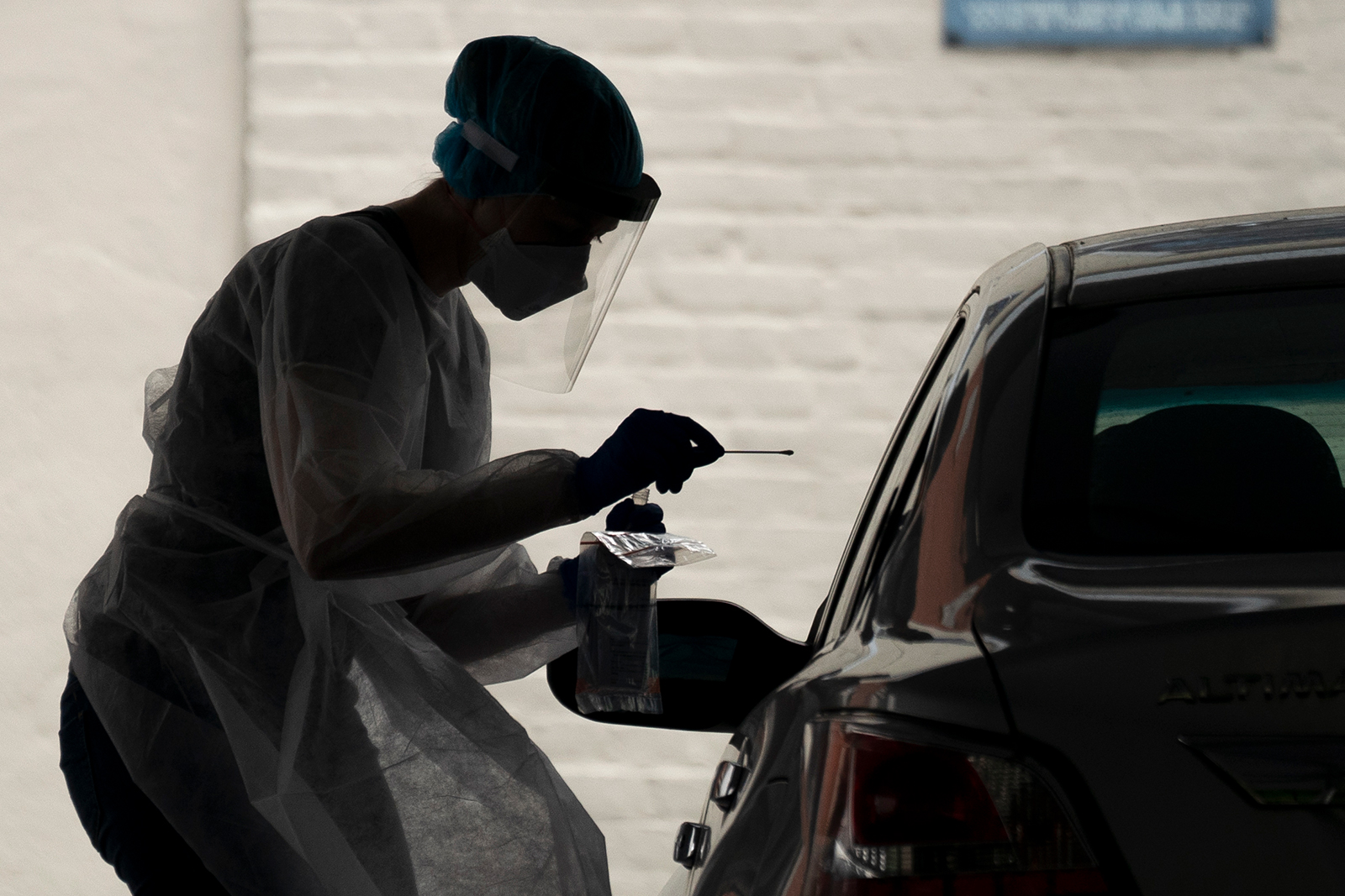 A healthcare worker administers a coronavirus test at a drive-thru testing site run by George Washington University Hospital in Washington, DC on May 26.