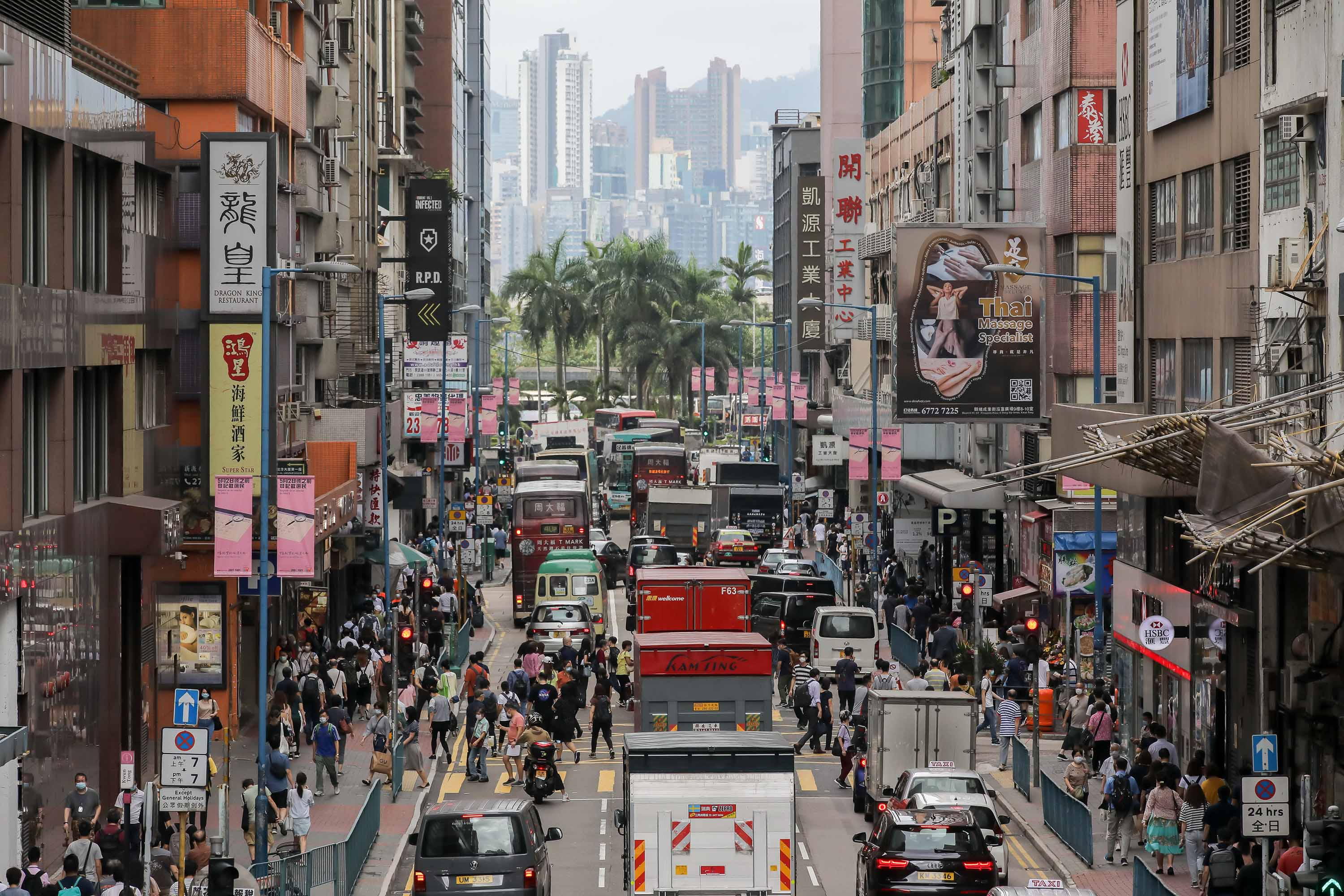 Pedestrians and vehicles make their way along a street in the Kwun Tong district of Hong Kong on May 6.