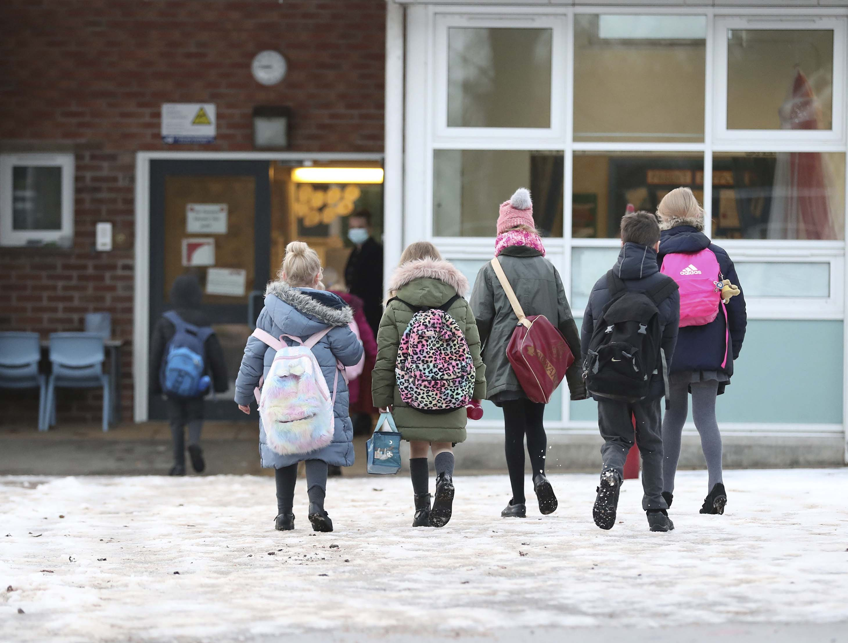 Pupils arrive at Manor Park School and Nursery in Knutsford, England, as some schools reopen on January 4 following the holiday break.