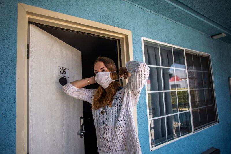 """A homeless woman puts on her mask at a motel room provided to homeless people under the """"Project Roomkey"""" program on April 26 in Venice Beach, California."""