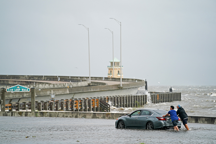 Two men help a stranded motorist in floodwaters on Monday,  August 30,  in Biloxi, Mississippi.