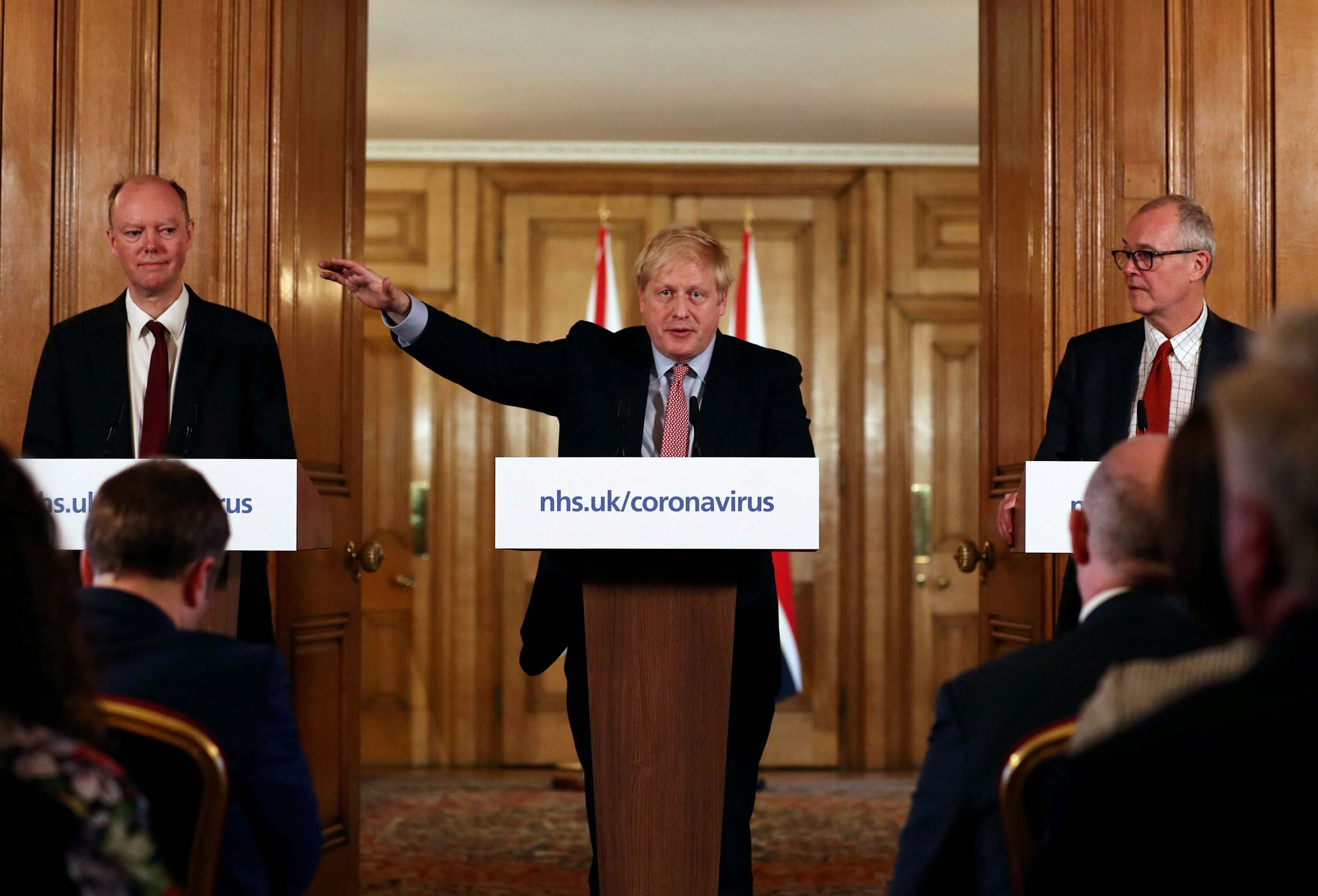 British Prime Minister Boris Johnson, center, speaks alongside Chief Medical Officer for England, Chris Whitty, left, and Government Chief Scientific Adviser, Sir Patrick Vallance during a news conference addressing the government's response to the novel coronavirus outbreak in London on March 12.