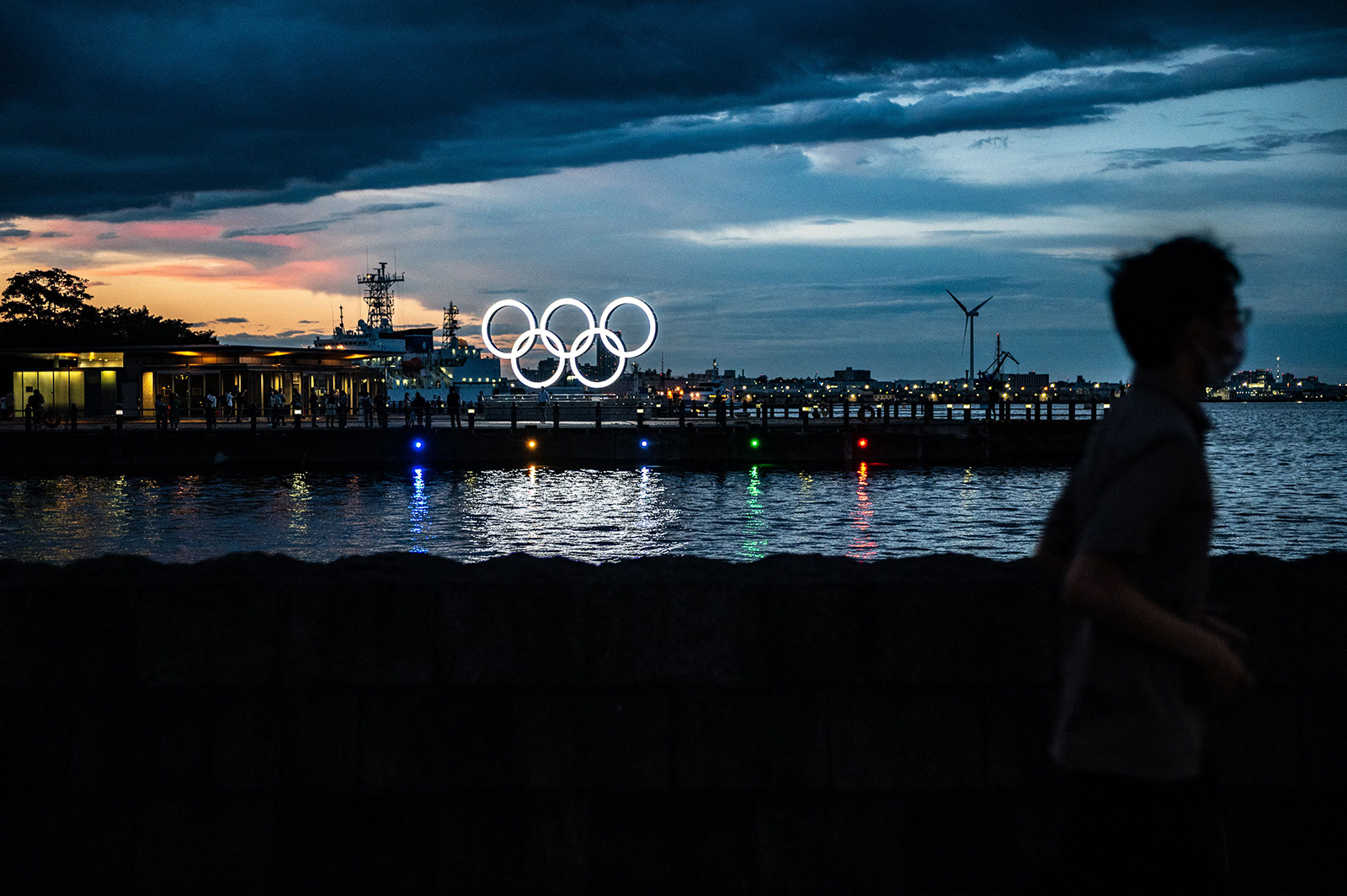 A man walks past the Olympic Rings lit up at dusk in Yokohama on July 27.