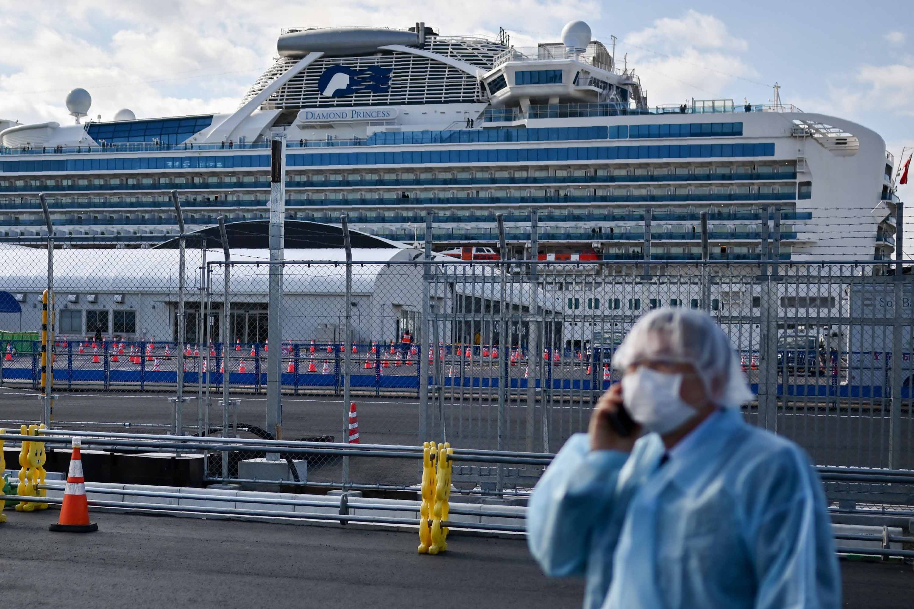 A man in protective gear speaks on a phone near the quarantined Diamond Princess cruise ship in Yokohama, Japan on \Wednesday.