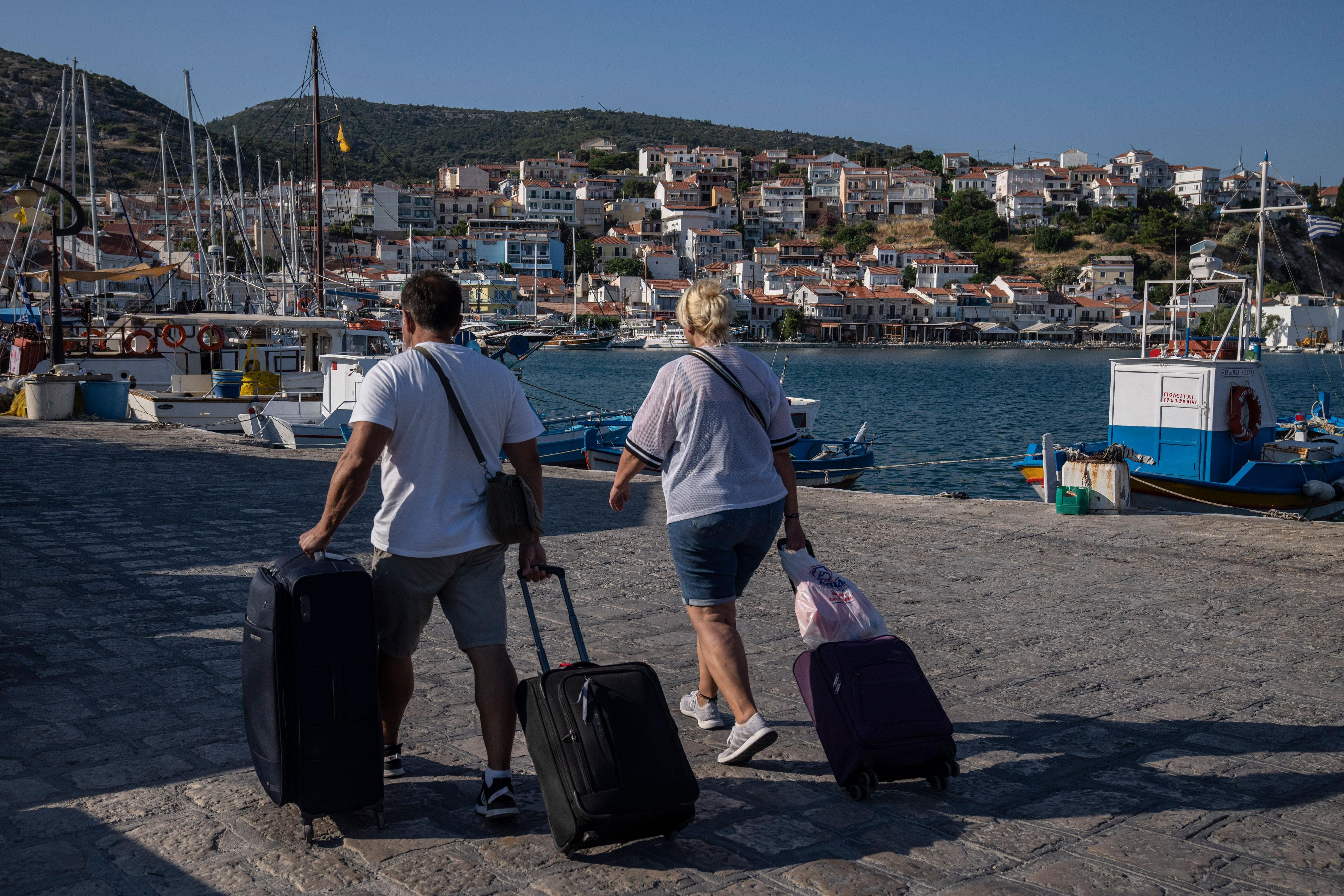 Travelers walk along the waterfront in Kokkari, on the eastern Aegean island of Samos, Greece, on Tuesday, June 8.