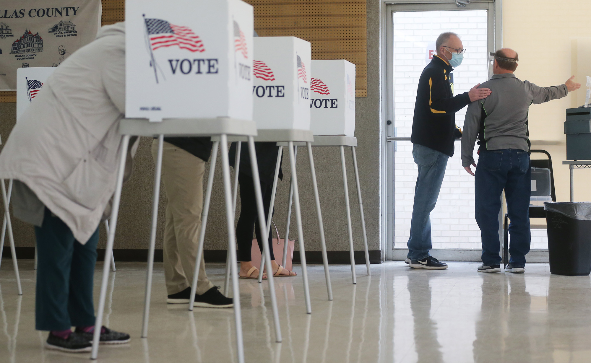 A voter speaks with an election official, right, after casting his ballot during early voting in the 2020 presidential election on October 29 in Adel, Iowa.