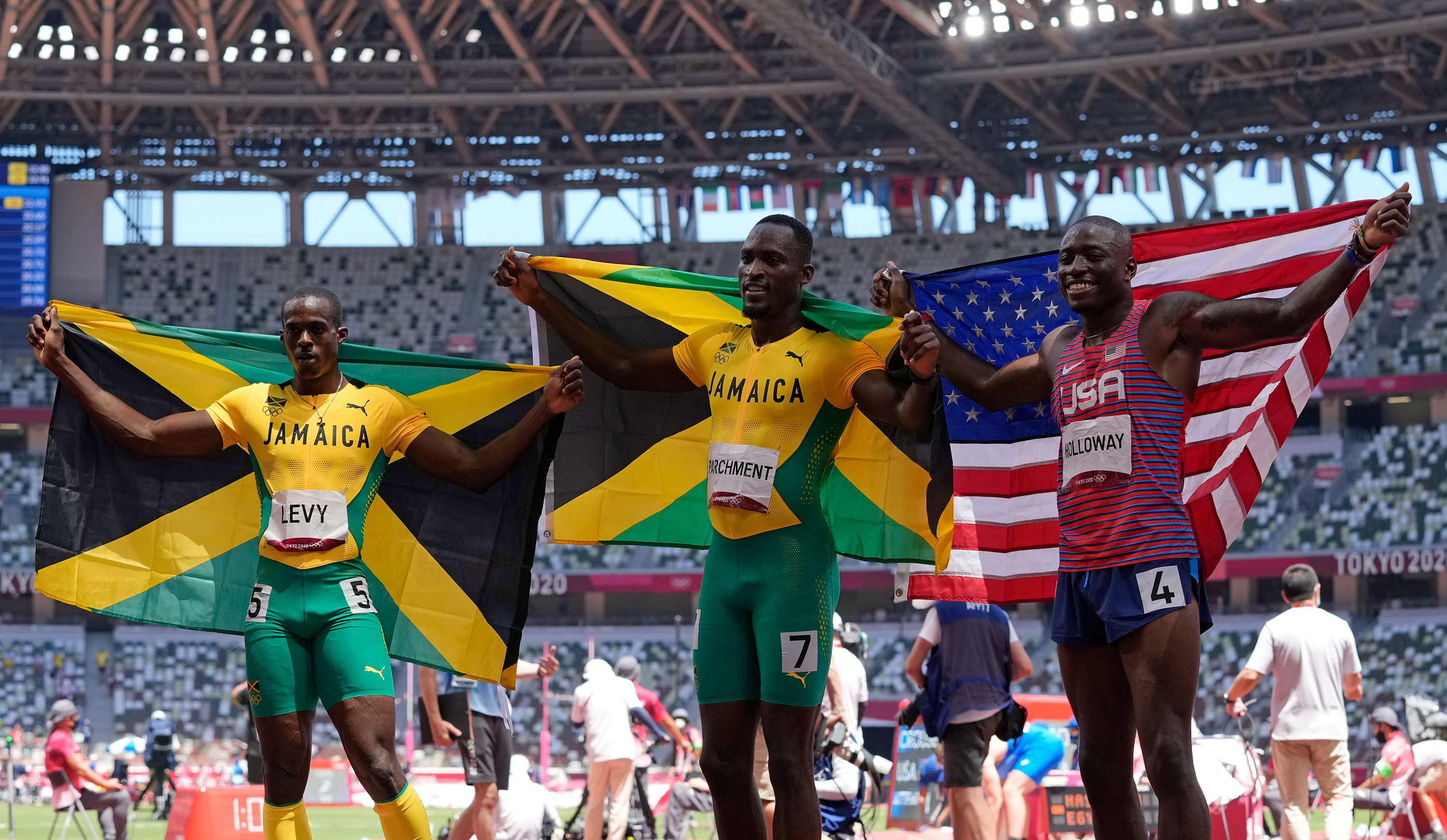 Jamaica's Hansle Parchment, center, celebrates winning the gold medal in the 110-meter hurdles alongside silver medalist Grant Holloway of the United States and bronze medalist Ronald Levy of Jamaica on August 5.