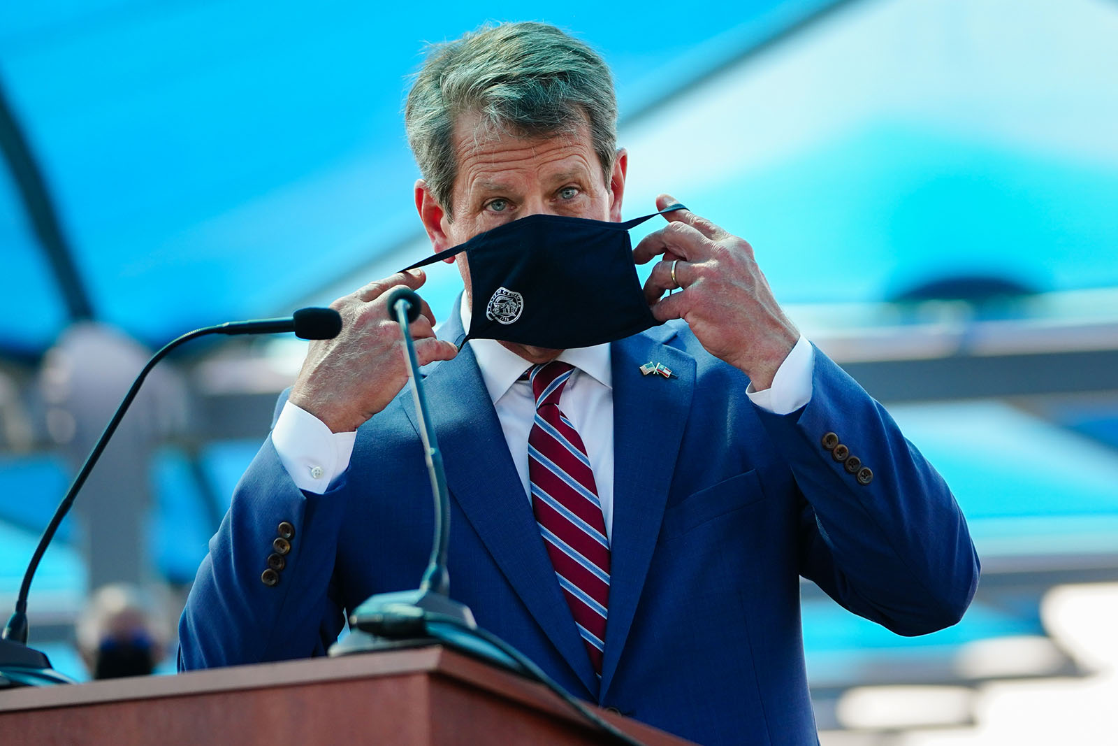 Georgia Governor Brian Kemp puts on a mask after speaking at a press conference announcing statewide expanded COVID testing on August 10, in Atlanta.