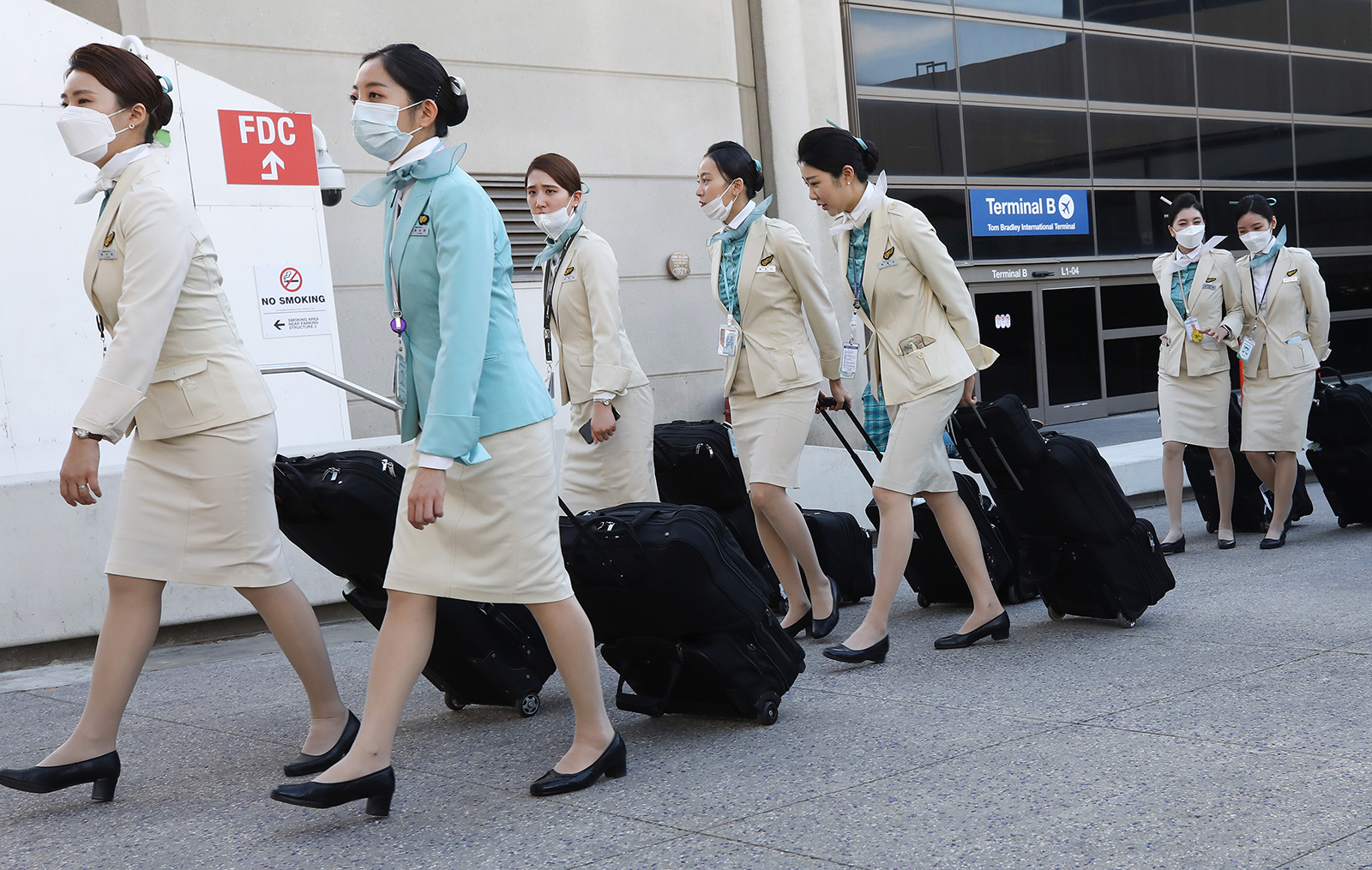 A flight crew from Korean Air, many wearing protective masks, depart the international terminal after arriving at Los Angeles International Airport on February 28, in Los Angeles.