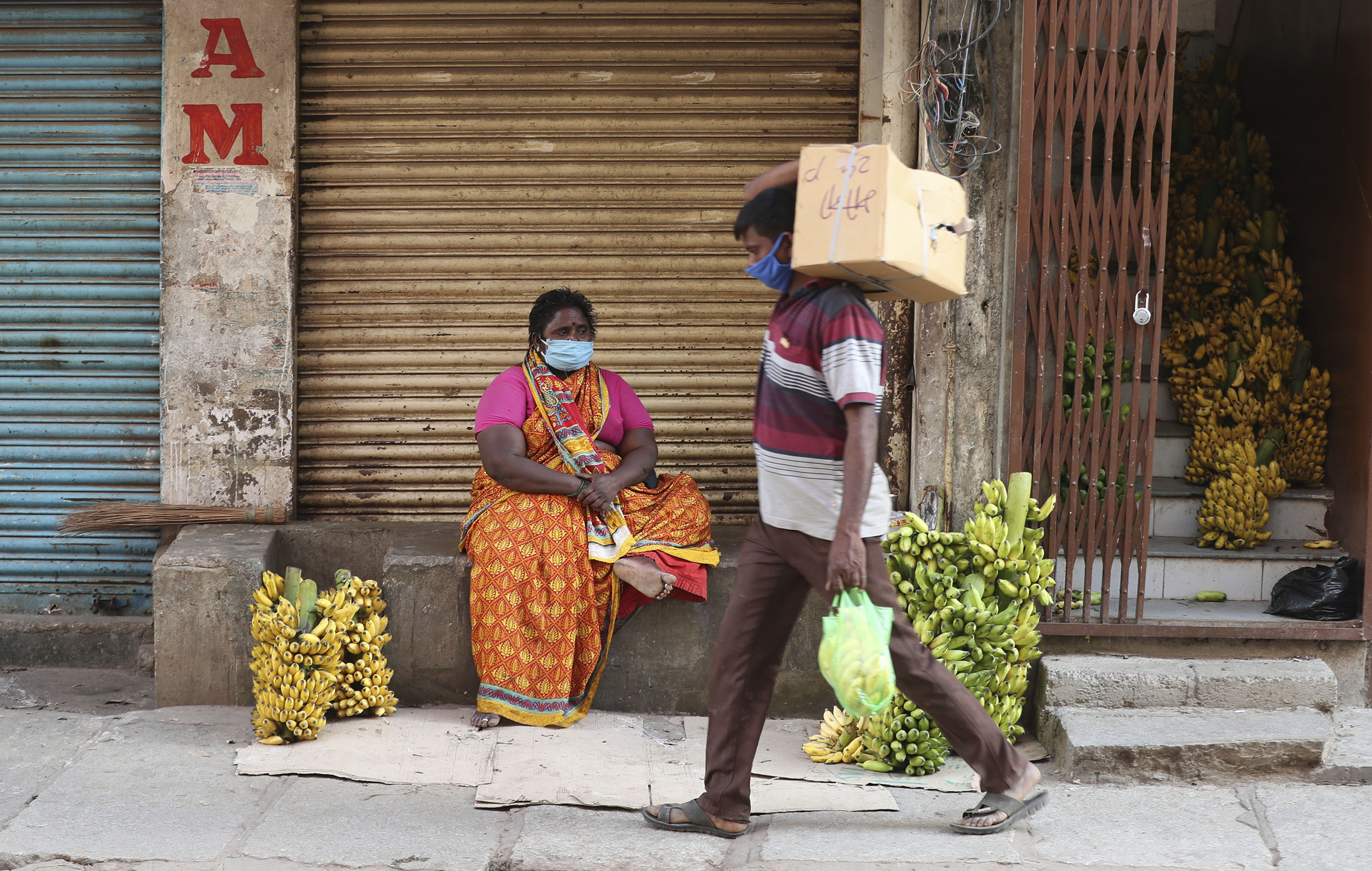 A banana vendor waits for buyers outside closed shops at a wholesale vegetable market which was closed after a recent spike in Covid-19 cases in Bengaluru, India, on Tuesday, June 23.