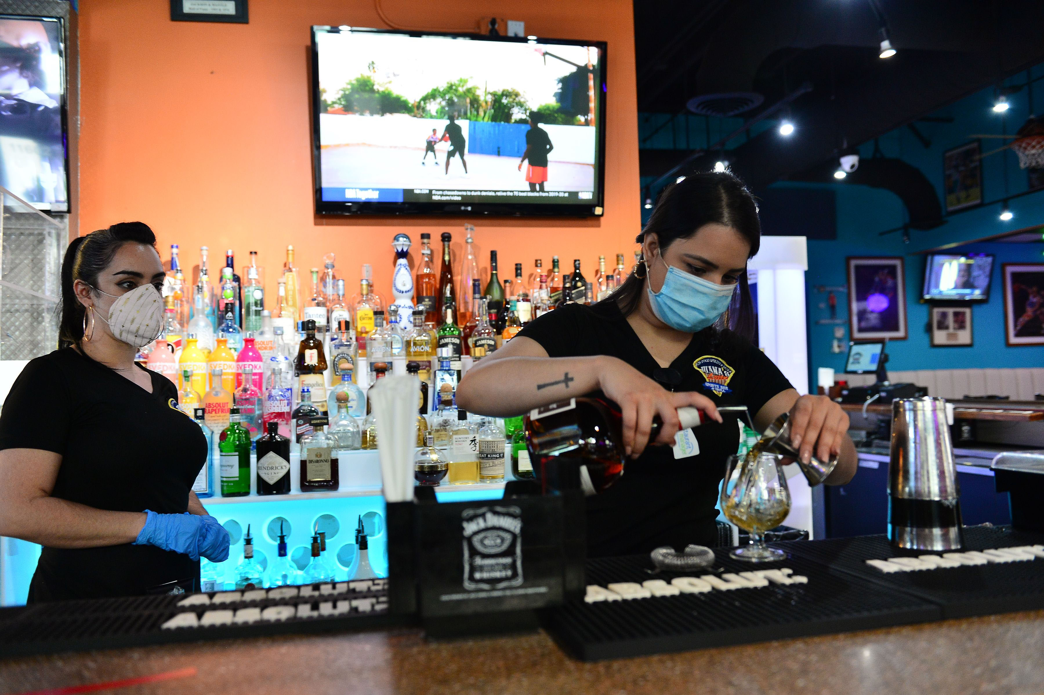 Bartenders prepare a drink for a customer at Juana's Latin Sports Bar & Grill in Miramar, Florida, on May 18.