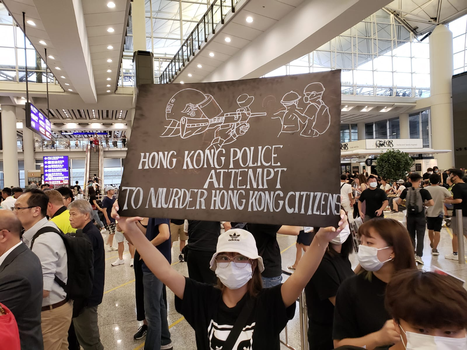 Protesters greet arriving travelers at the airport with signs warning of police brutality.