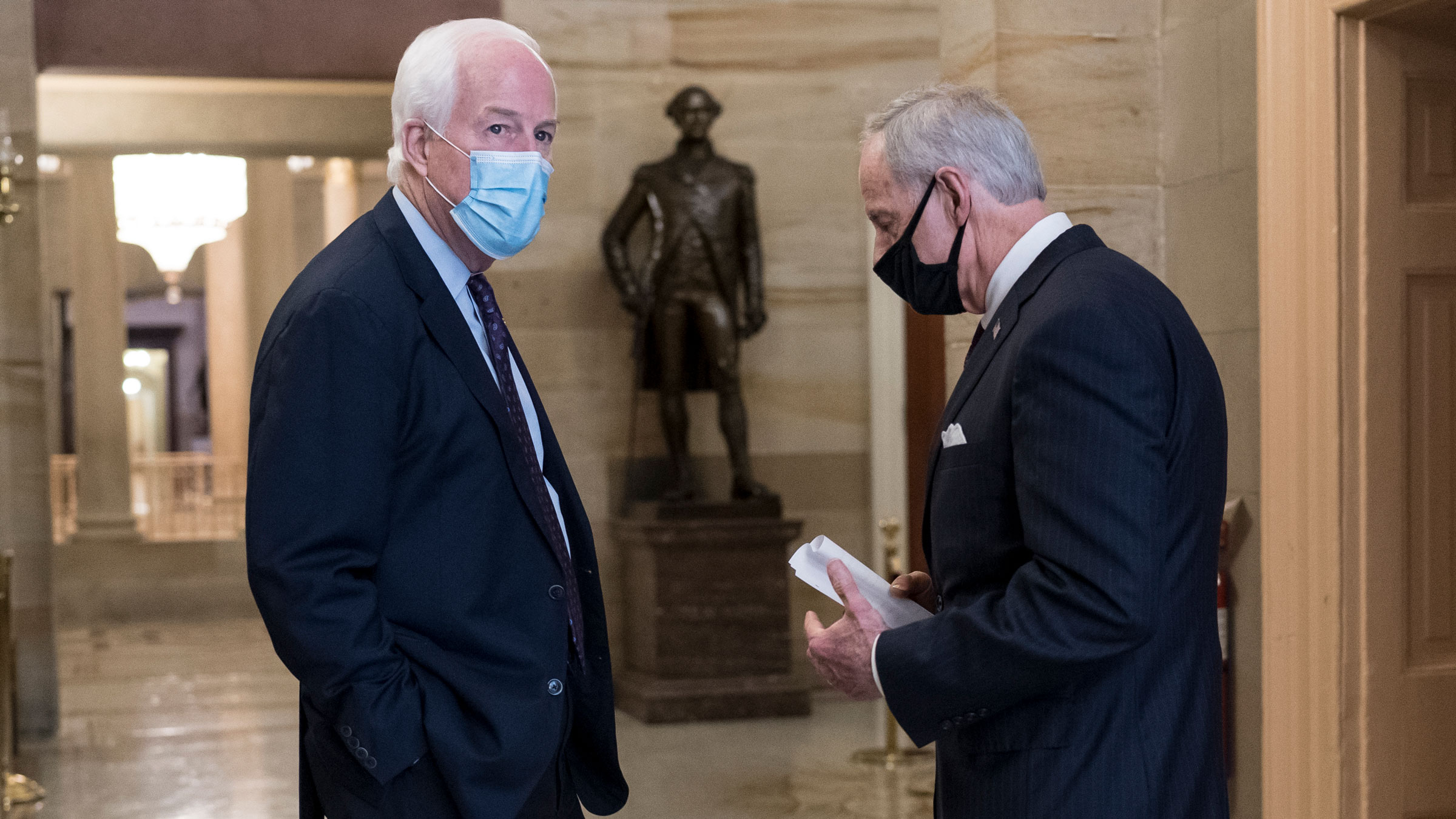 US Sen. John Cornyn, left, talks with Sen. Tom Carper in a corridor near the Senate chamber.