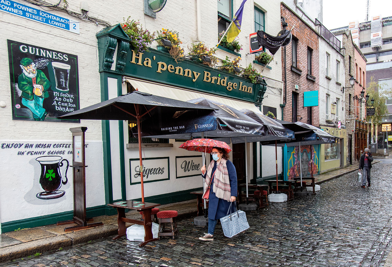 A pedestrian wearing a face mask walks past a pub in Dublin on October 19.