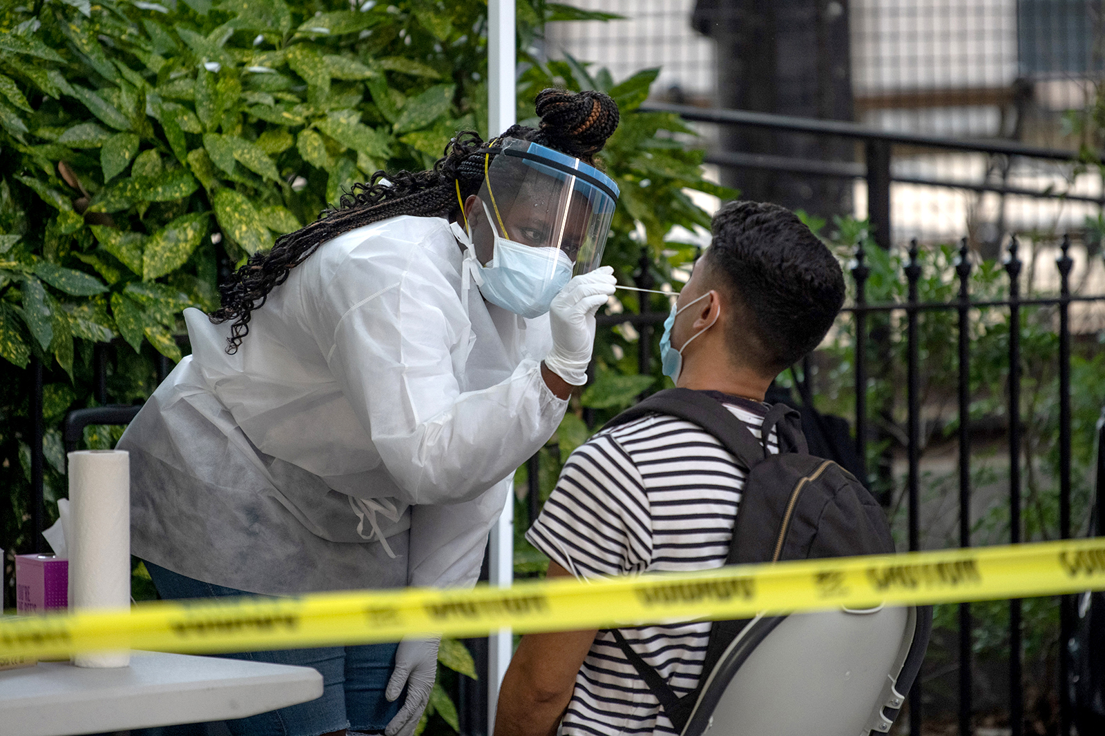 A medical worker wearing PPE administers a nasal swab test at a free coronavirus testing location outside Washington Square Park in New York on July 18.