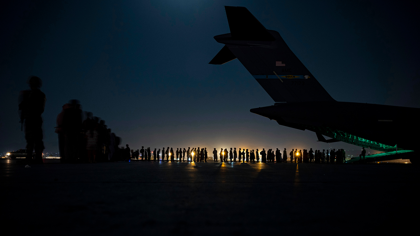 In this image provided by the U.S. Air Force, U.S. Air Force aircrew, assigned to the 816th Expeditionary Airlift Squadron, prepare to load qualified evacuees aboard a U.S. Air Force C-17 Globemaster III aircraft in support of the Afghanistan evacuation at Hamid Karzai International Airport in Afghanistan on August 21.