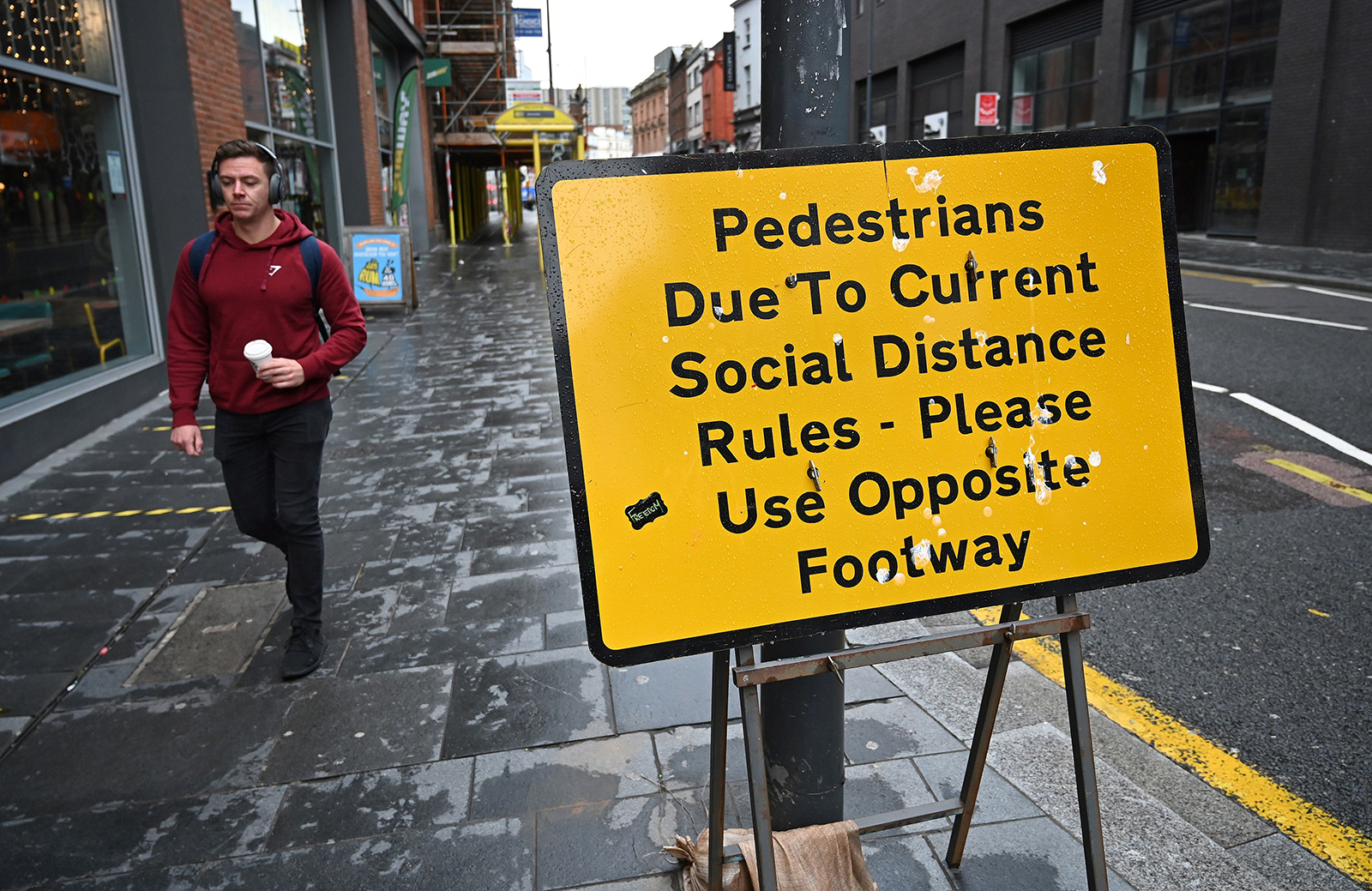 A pedestrian walks near a street sign reminding members of the public to adhere to social distancing guidelines in Liverpool, England, on October 12.