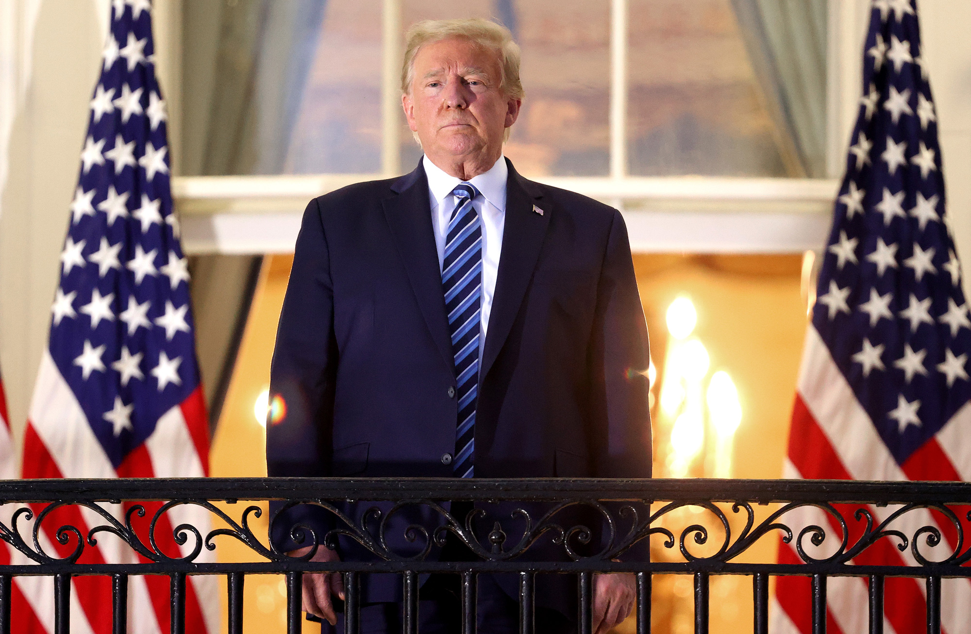 President Donald Trump stands on the Truman Balcony after returning to the White House from Walter Reed National Military Medical Center on October 5 in Washington, DC.