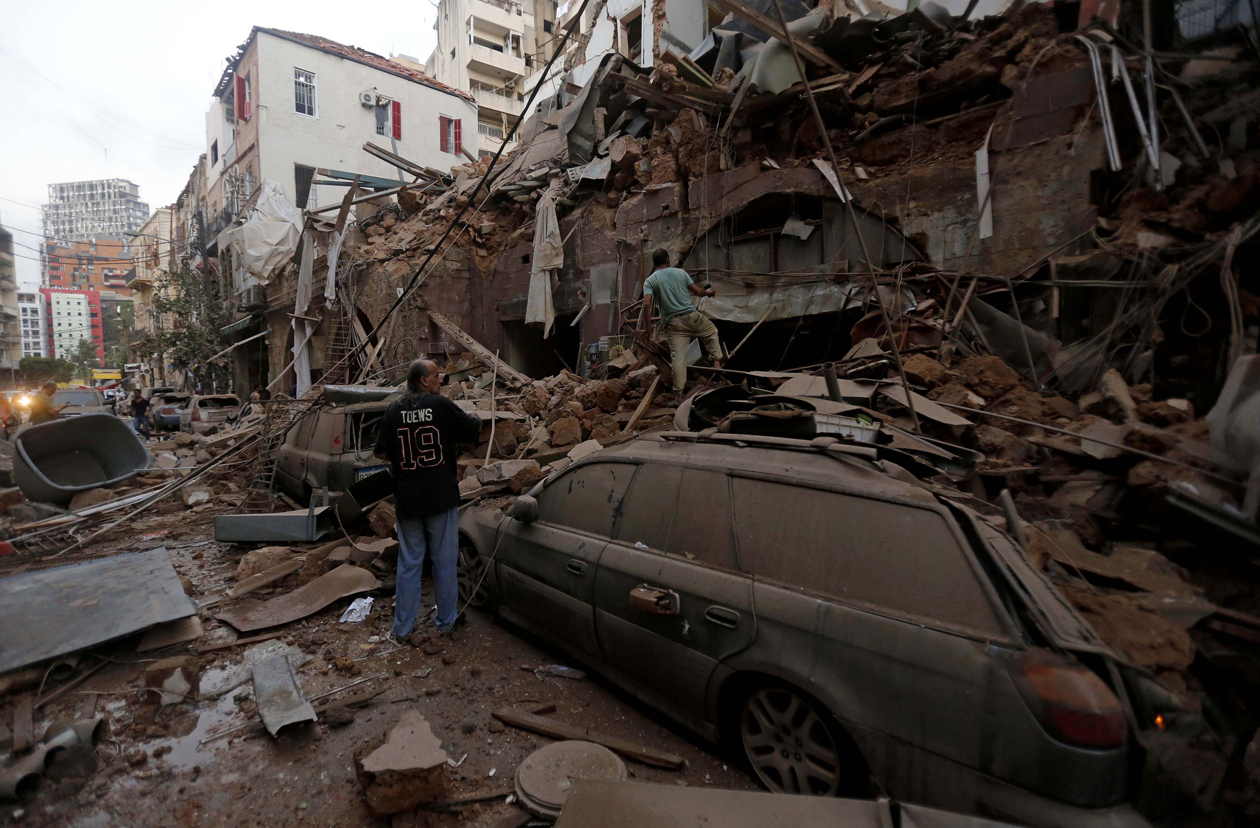 People stand on a pile of rubble in Beirut on August 4.