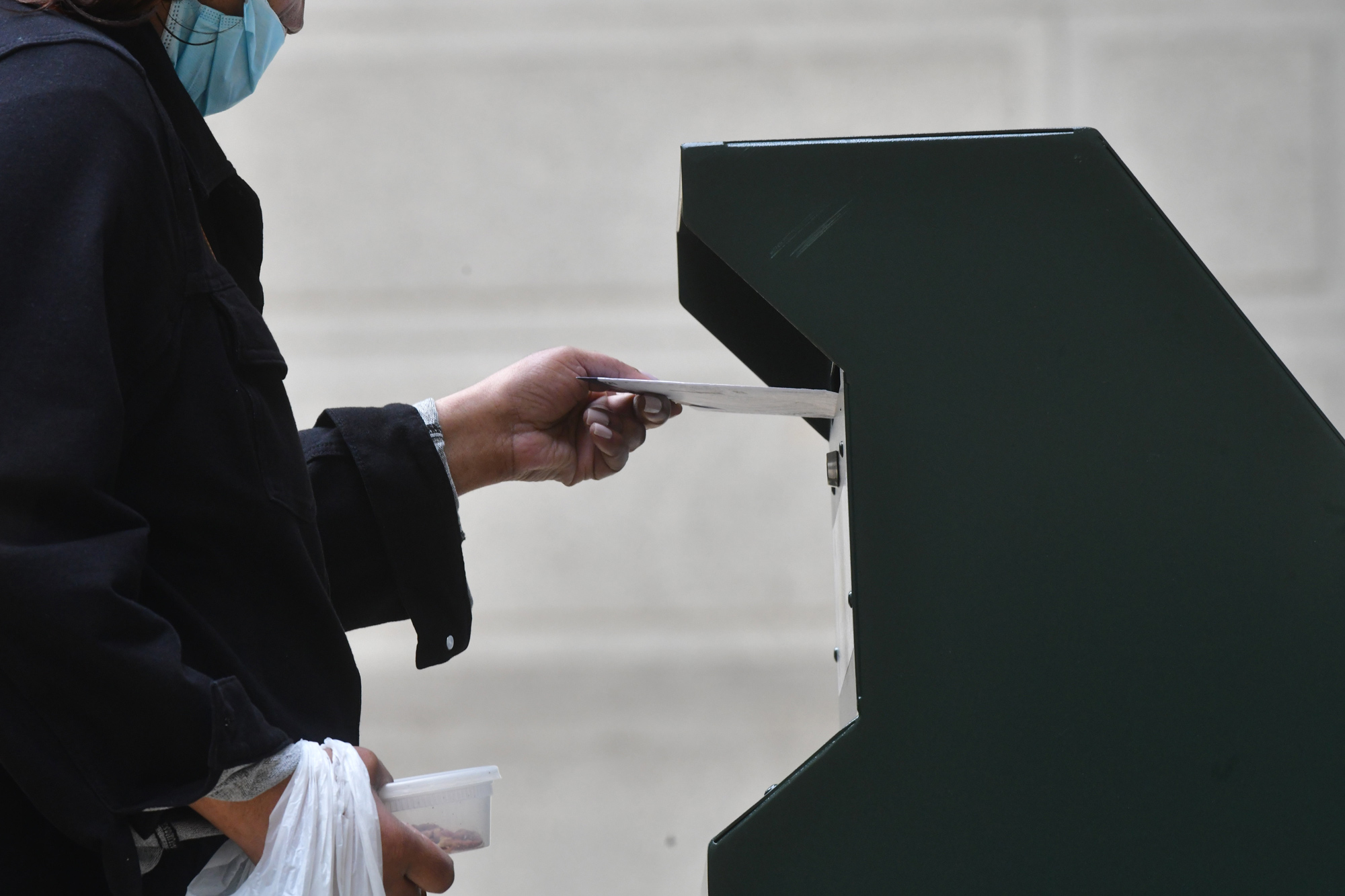 A woman deposits her ballot in an official ballot drop box at the satellite polling station outside Philadelphia City Hall on October 27 in Philadelphia.