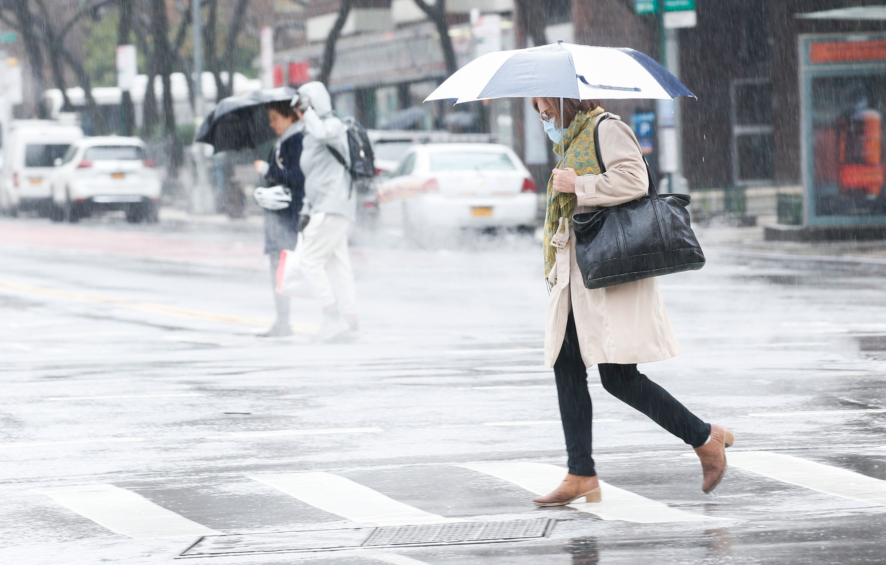 A woman wearing a facemask crosses the street on March 28 in New York City.