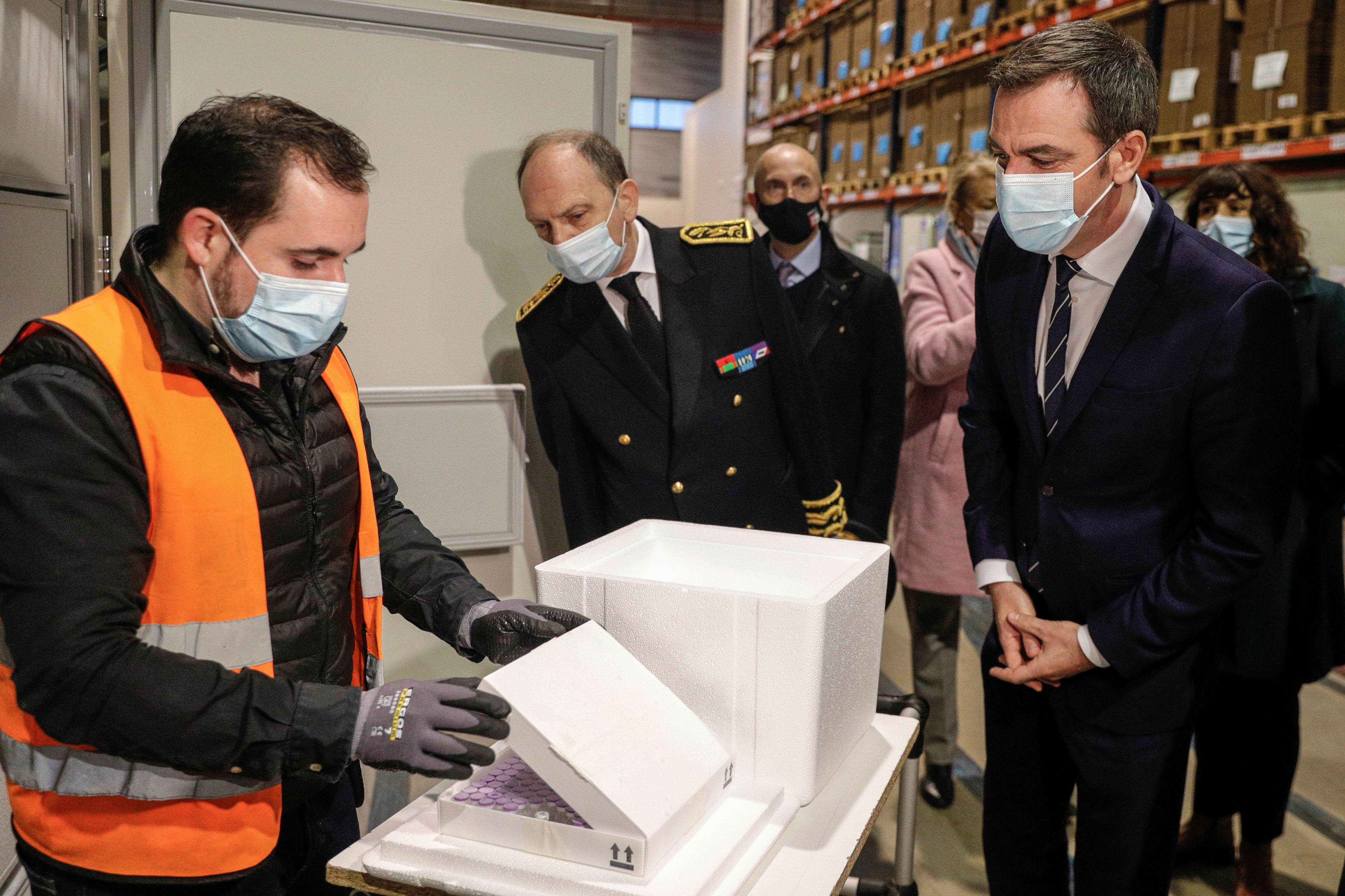 French Health Minister Olivier Véran, right, looks at a box containing the Pfizer/BioNTech Covid-19 vaccine while visiting a distribution center in Chanteloup-en-Brie, France, on December 22.
