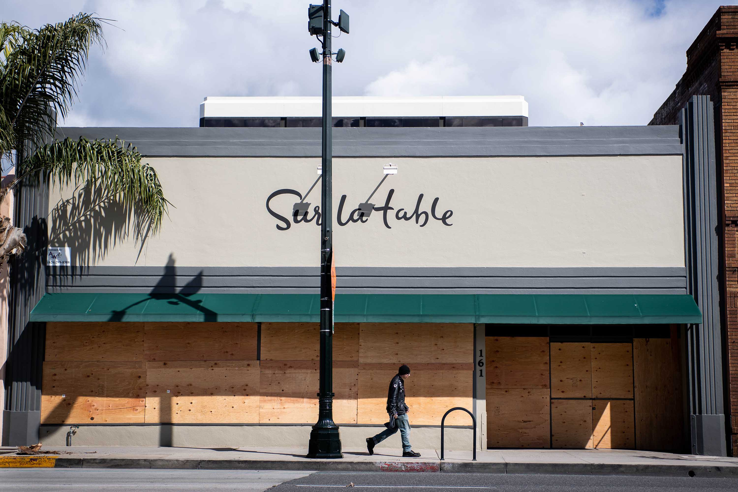 A pedestrian passes a boarded up Sur La Table retail space in Pasadena, California, on March 23.