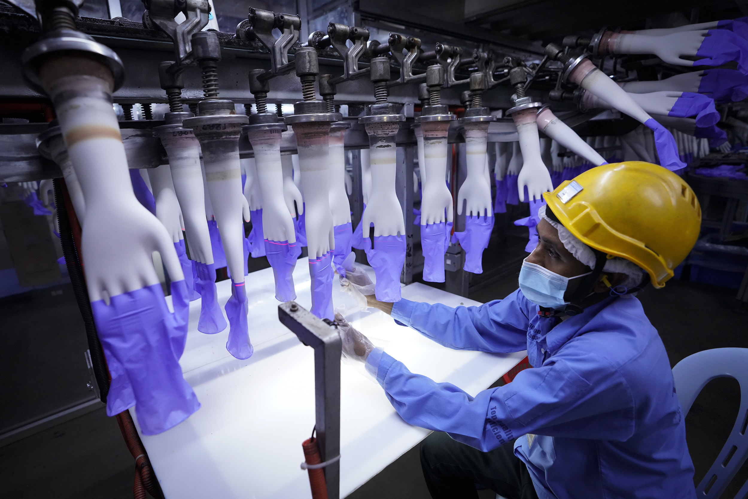 A worker inspects disposable gloves at the Top Glove factory in Shah Alam on the outskirts of Kuala Lumpur, Malaysia, on Wednesday, August 26.