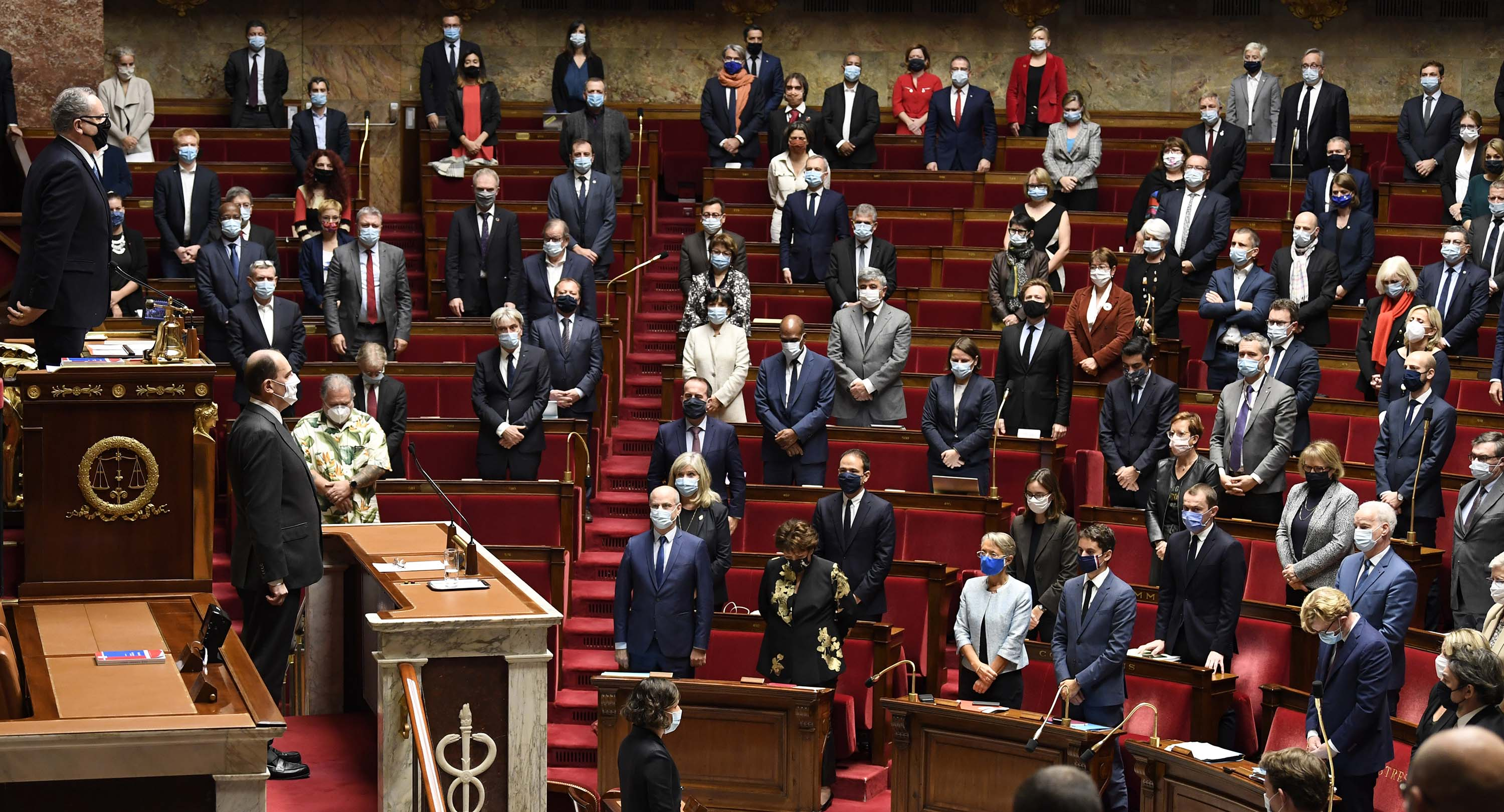 French Prime Minister Jean Castex (second from left, behind the lower desk) leads lawmakers in a moment of silence at the National Assembly in Paris on Thursday, in tribute to the victims of a knife attack in Nice.