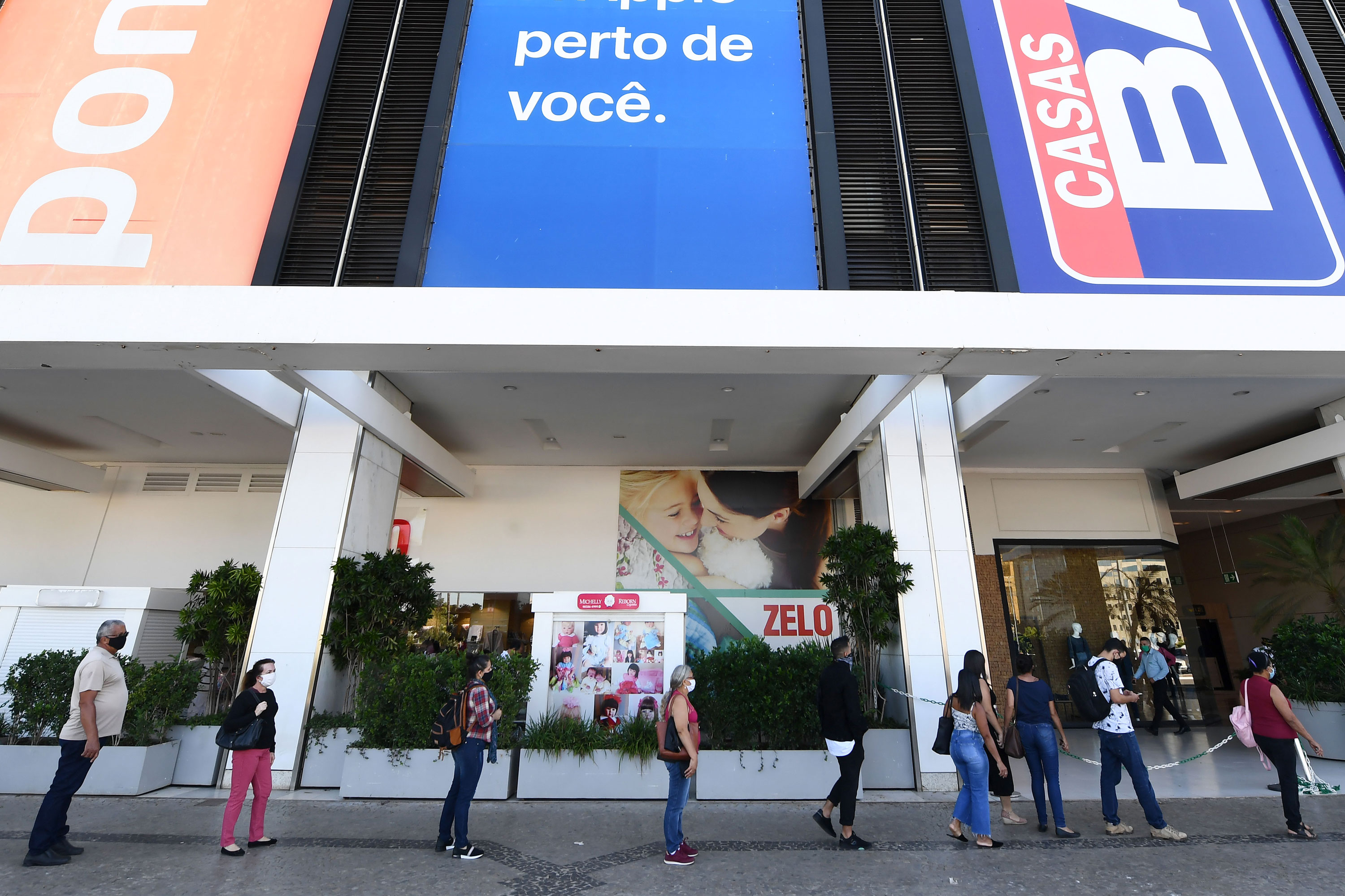 People wait in line to have their body temperature checked before entering a shopping mall in Brasilia, Brazil, on May 27.
