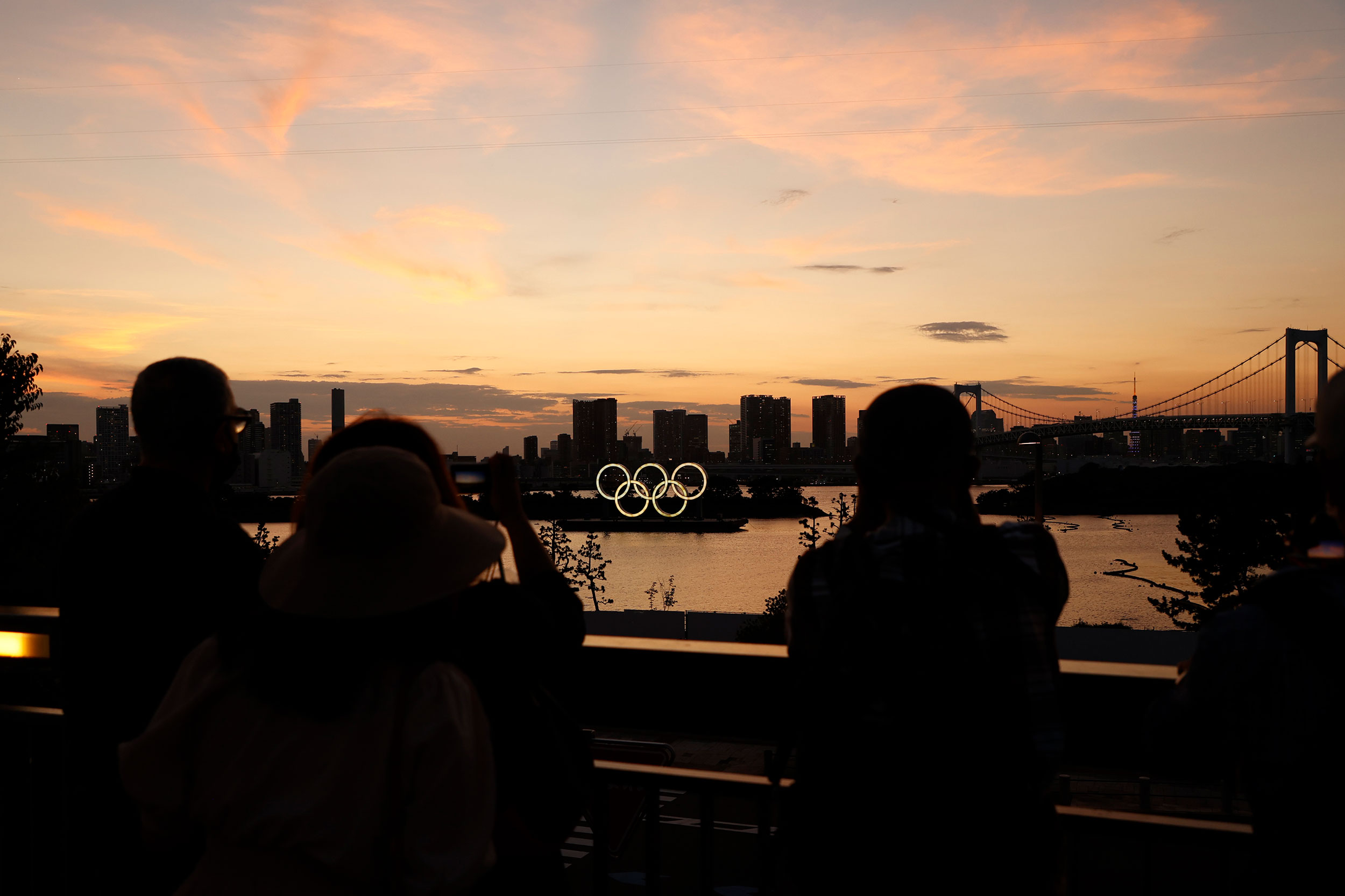 People take photos of the Olympic rings displayed at Odaiba Marine Park in Tokyo on July 19.