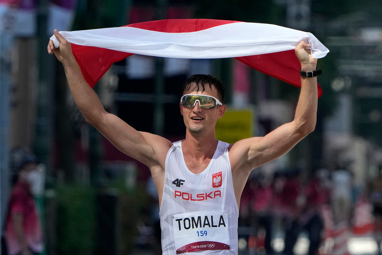 Poland's Dawid Tomala celebrates after winning gold in the 50 kilometers race walk on Friday.